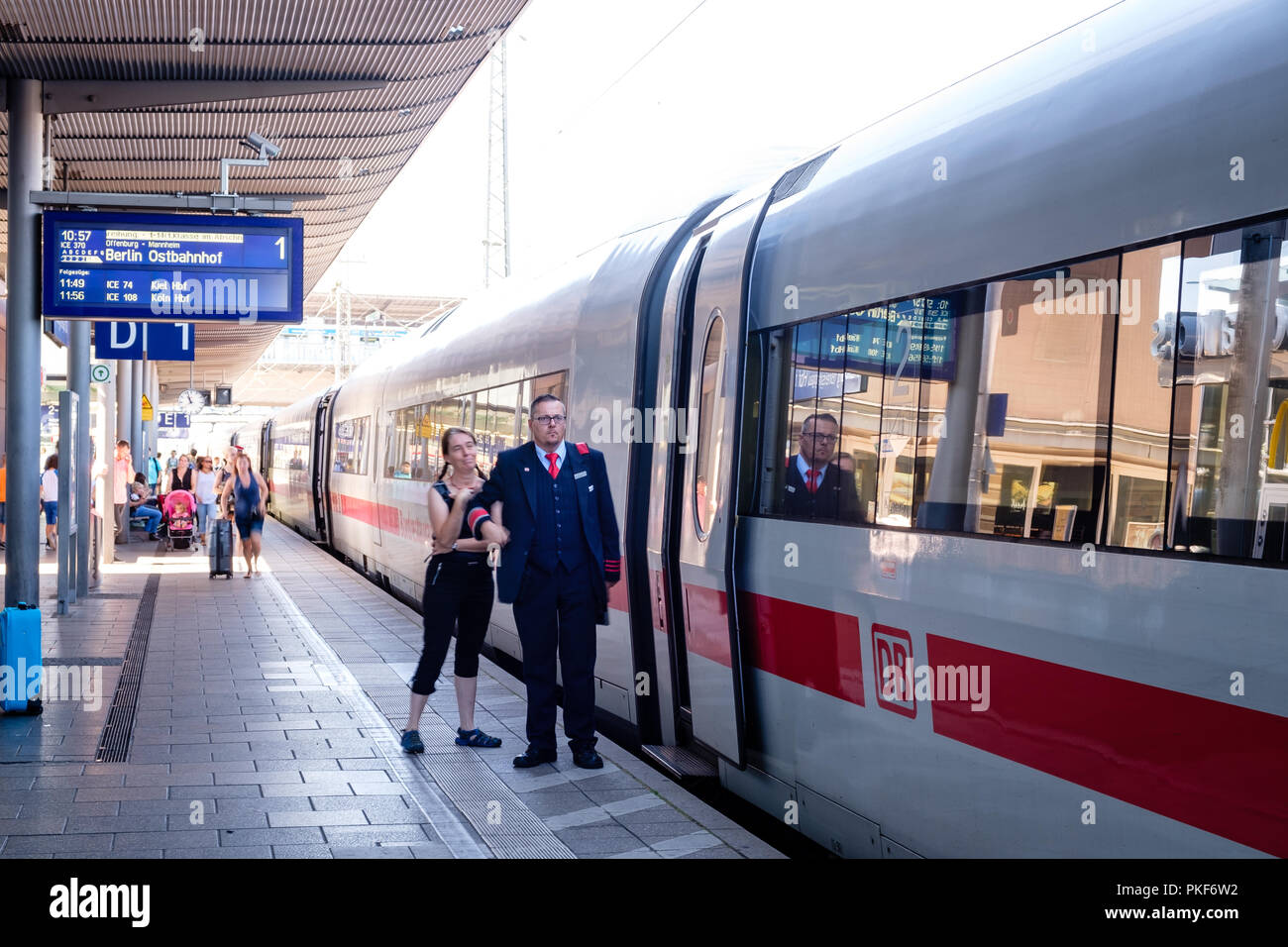 Freiburg, Baden-Wurttemberg, Germany - JULY 30 2018 : Railway guard on the platform next to open door of ICE high speed Intercity-Express train. - Stock Image