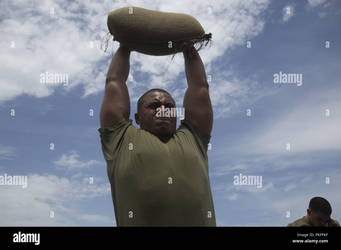 PACIFIC OCEAN (August 1, 2018) – U.S. Marine Lance Cpl. Erick Flores-Garcia a machine gunner with Battalion Landing Team 3/1, 13th Marine Expeditionary Unit (MEU), shoulder presses a sand bag in a Marine Corps Martial Arts Program course aboard the San Antonio-class amphibious transport dock USS Anchorage (LPD 23), during a regularly scheduled deployment of the Essex Amphibious Ready Group (ARG) and 13th MEU. The Essex ARG/MEU team is a strong, flexible, responsive and consistent force capable of maneuver warfare across all domains; it is equipped and scalable to respond to any crisis from hum - Stock Image