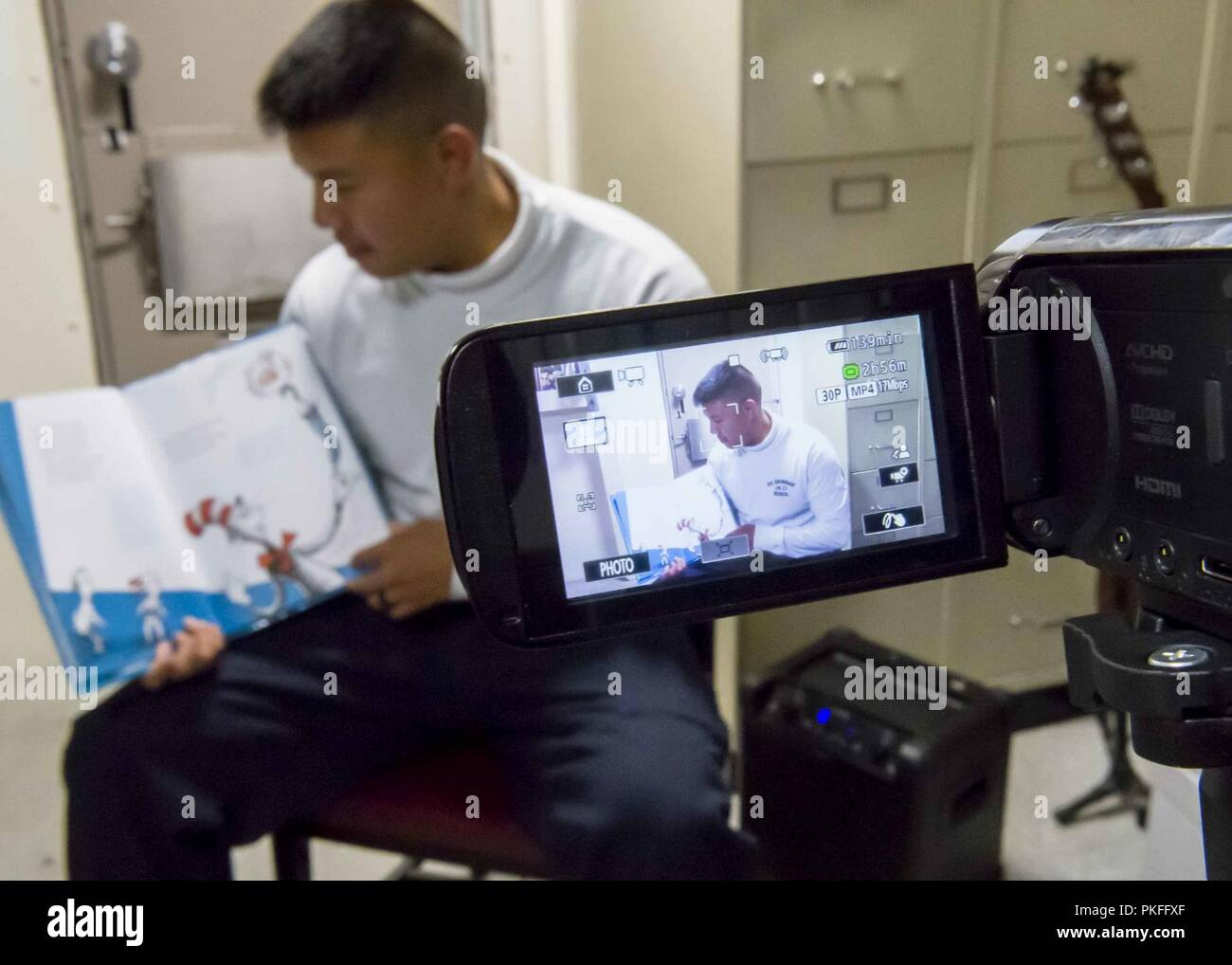 PACIFIC OCEAN (July 26, 2018) Hospital Corpsman 3rd Class Rene Cruz, from Seattle, reads a book to his child in the medical ward of San Antonio-class amphibious transport dock USS Anchorage (LPD 23) during a regularly scheduled deployment of Essex Amphibious Ready Group (ARG) and 13th Marine Expeditionary Unit (MEU). The Essex ARG/MEU team is a strong and flexible force equipped and scalable to respond to any crisis ranging from humanitarian assistance and disaster relief to contingency operations. - Stock Image
