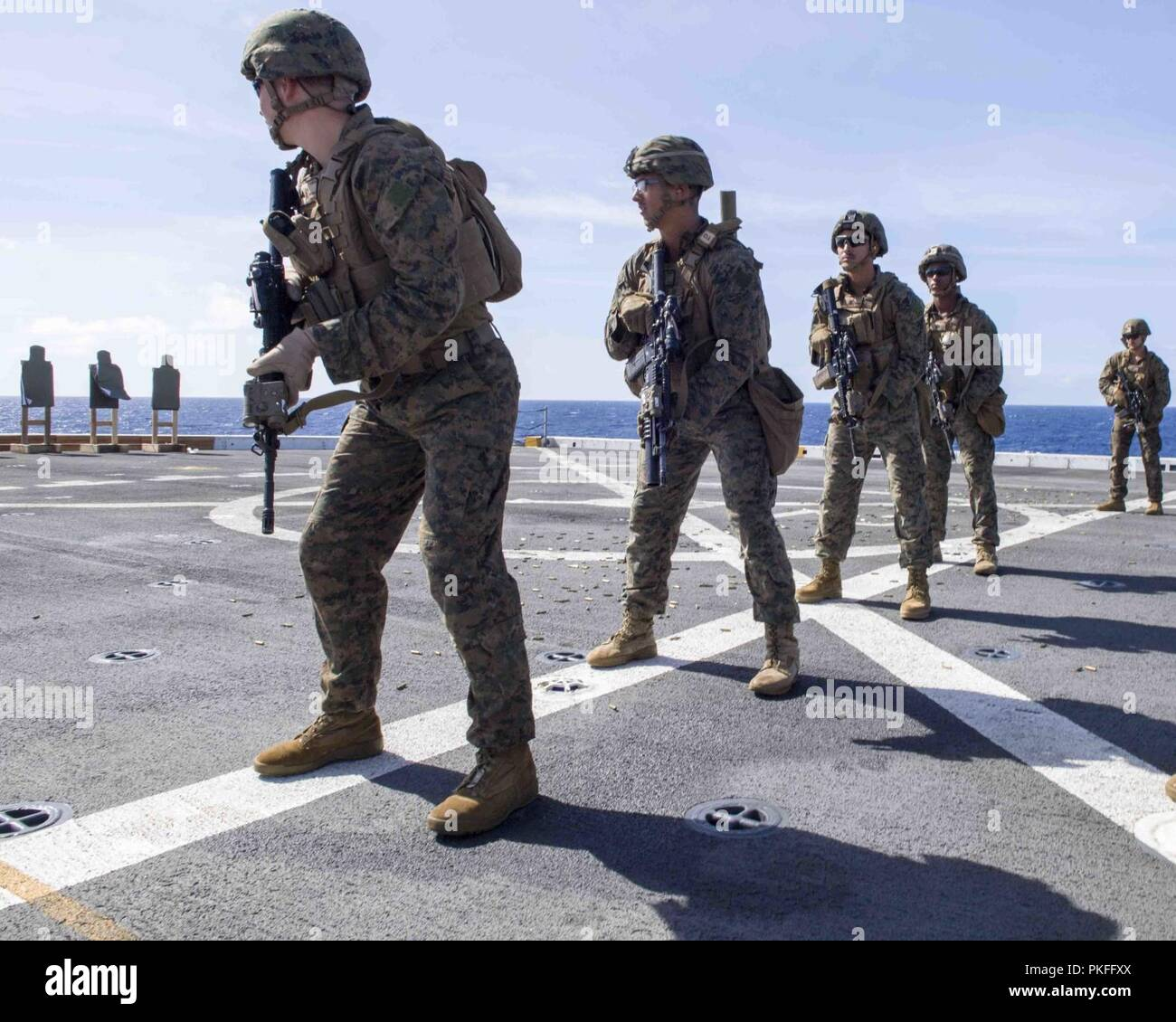 PACIFIC OCEAN (July 29, 2018) Marines assigned to the 13th Marine Expeditionary Unit (MEU), participate in a gun shoot training exercise on the flight deck of during a regularly scheduled deployment of Essex Amphibious Ready Group (ARG) and 13th Marine Expeditionary Unit (MEU). The Essex ARG/MEU team is a strong and flexible force equipped and scalable to respond to any crisis ranging from humanitarian assistance and disaster relief to contingency operations. - Stock Image