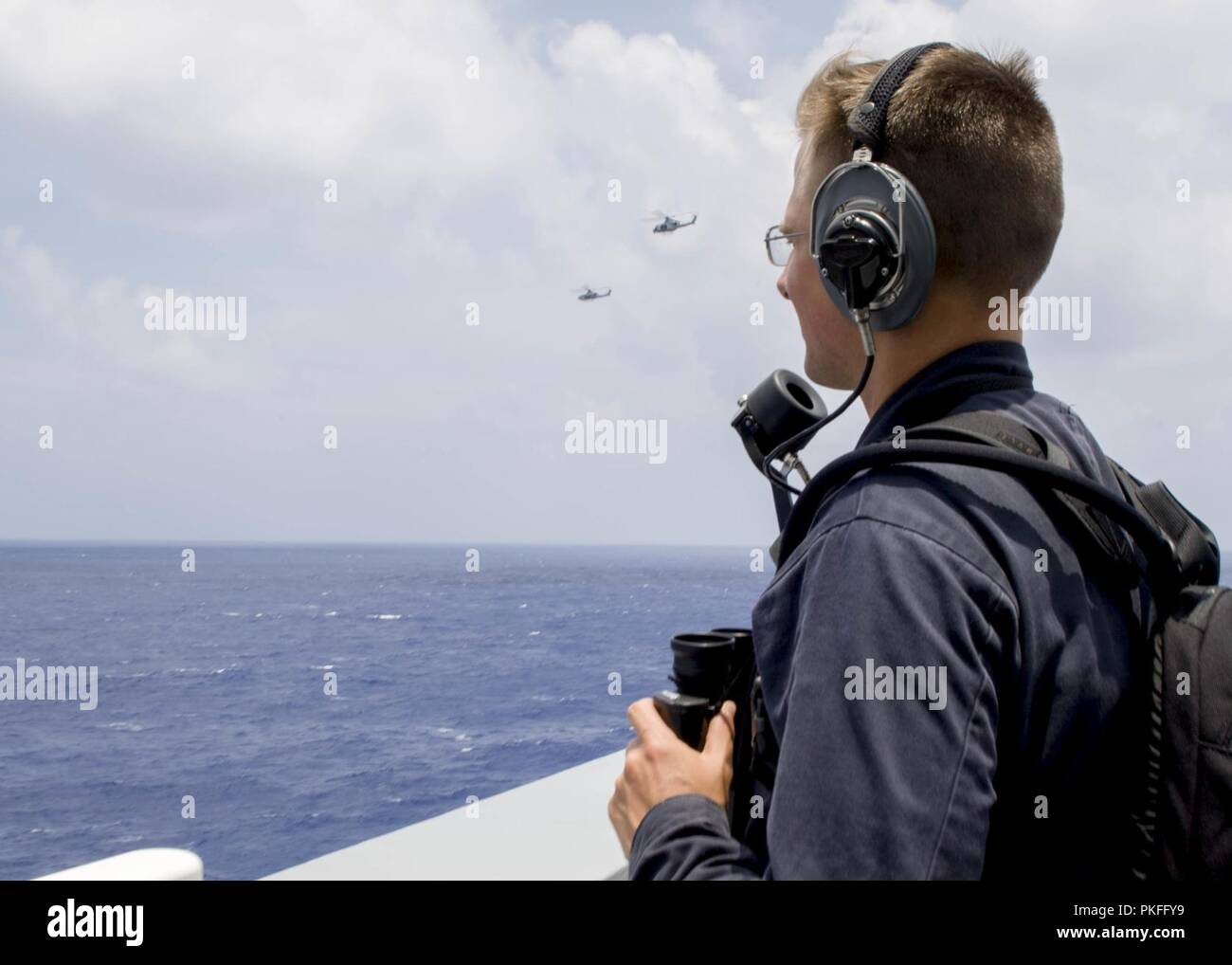 PACIFIC OCEAN (August 9, 2018) Seaman Spencer Englert, from Wichita, Kan., stands look out watch aboard San Antonio-class amphibious transport dock USS Anchorage (LPD 23) during a regularly scheduled deployment of the Essex Amphibious Ready Group (ARG) and 13th Marine Expeditionary Unit (MEU). The Essex ARG/MEU team is a strong and flexible force equipped and scalable to respond to any crisis ranging from humanitarian assistance and disaster relief to contingency operations. - Stock Image
