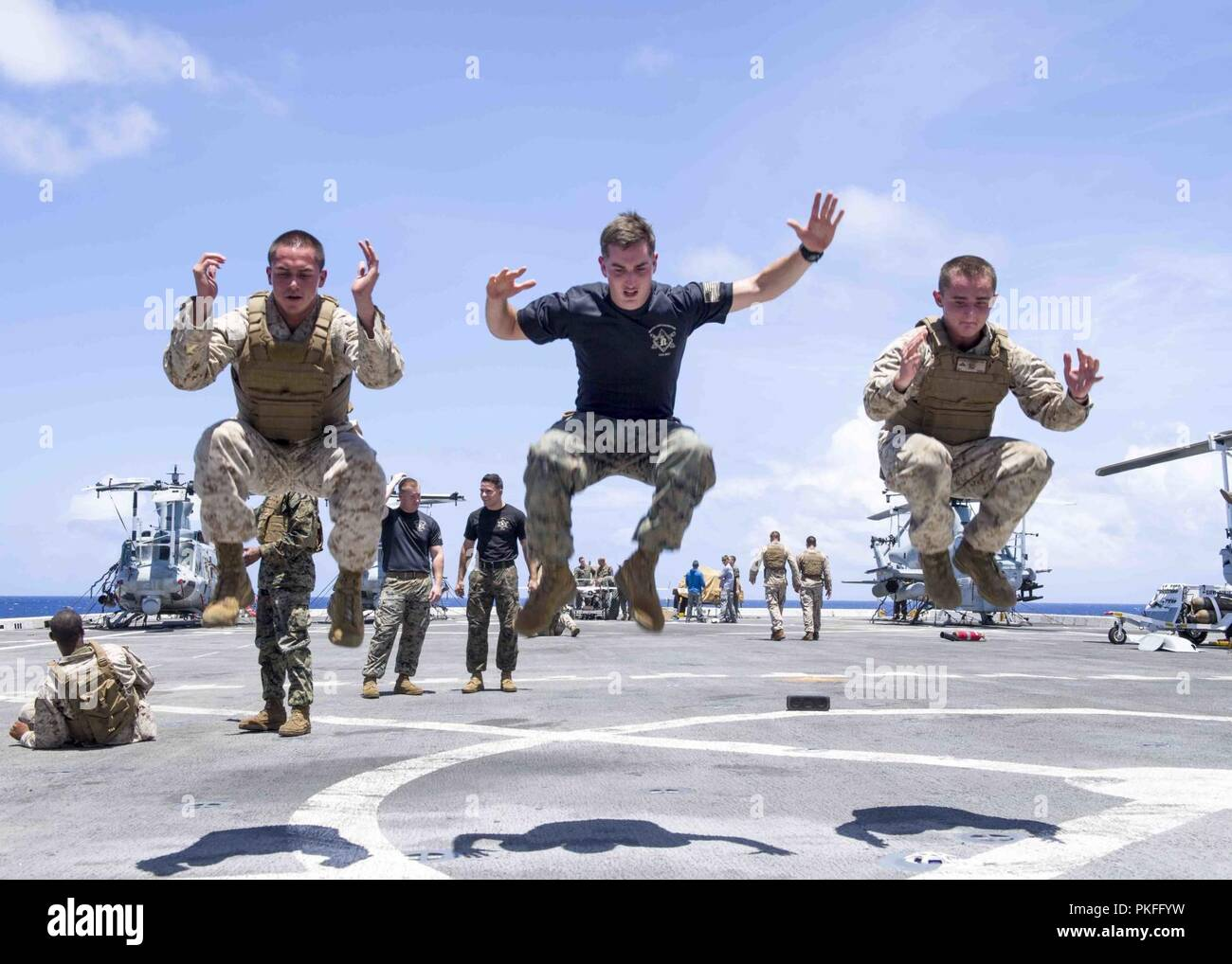 PACIFIC OCEAN (August 6, 2018) Marines assigned to 13th Marine Expeditionary Unit (MEU) conduct physical training on the flight deck of San Antonio-class amphibious transport dock USS Anchorage (LPD 23) during a regularly scheduled deployment of the Essex Amphibious Ready Group (ARG) and 13th MEU. The Essex ARG/MEU team is a strong and flexible force equipped and scalable to respond to any crisis ranging from humanitarian assistance and disaster relief to contingency operations. - Stock Image