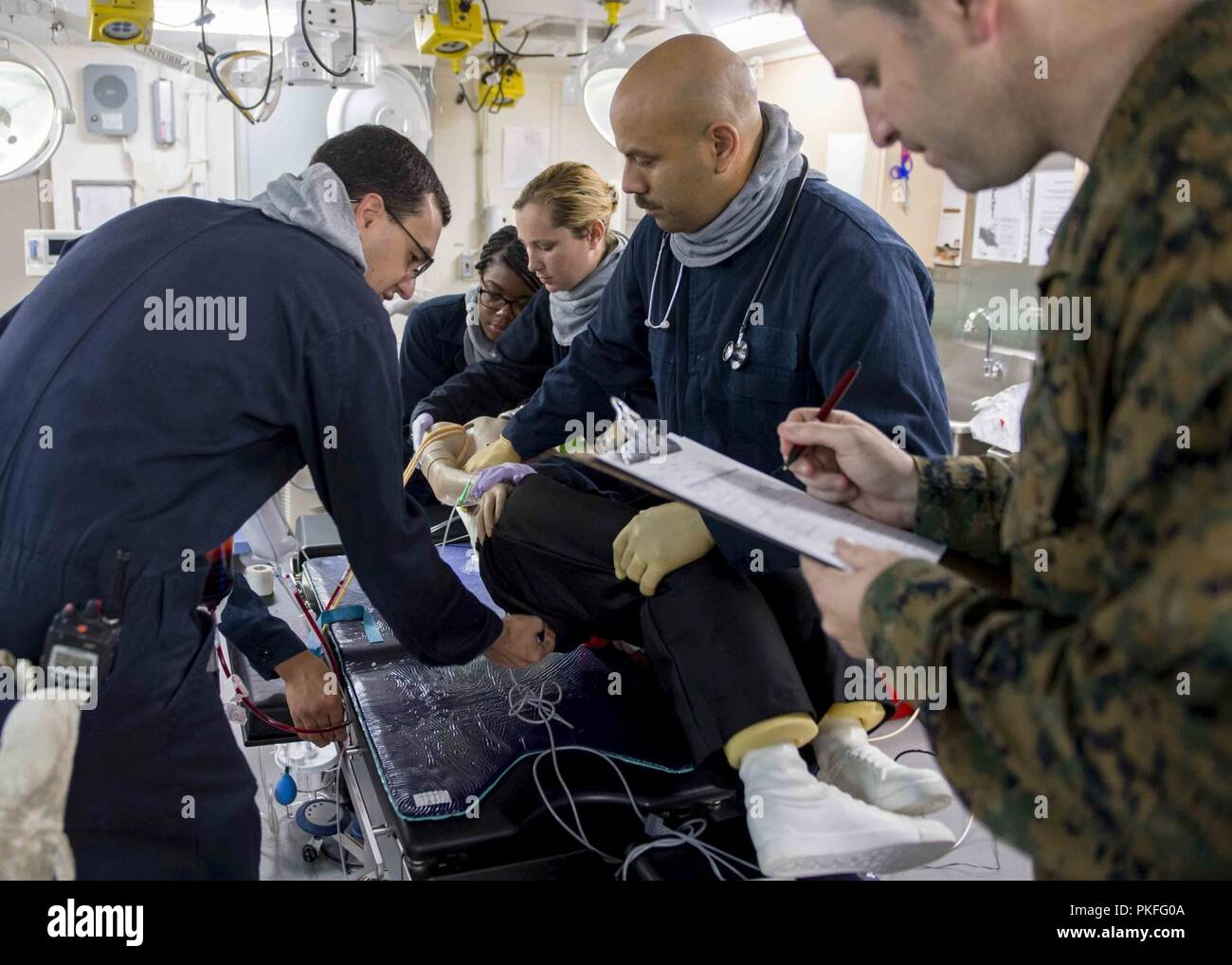 PACIFIC OCEAN (August 4, 2018) Sailors conduct medical emergency response training in the medical ward aboard San Antonio-class amphibious transport dock USS Anchorage (LPD 23) during a regularly scheduled deployment of the Essex Amphibious Ready Group (ARG) and 13th Marine Expeditionary Unit (MEU). The Essex ARG/MEU team is a strong and flexible force equipped and scalable to respond to any crisis ranging from humanitarian assistance and disaster relief to contingency operations. - Stock Image
