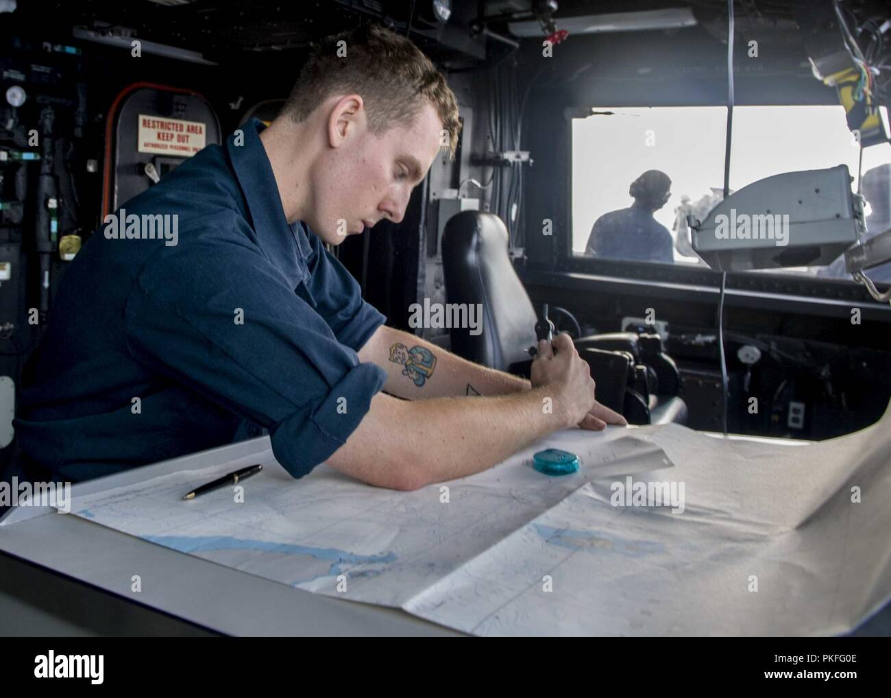 PACIFIC OCEAN (August 8, 2018) Quartermaster Seaman Keegan Taylor, from Houston, plots navigational charts in the pilot house of San Antonio-class amphibious transport dock USS Anchorage (LPD 23) during a regularly scheduled deployment of the Essex Amphibious Ready Group (ARG) and 13th Marine Expeditionary Unit (MEU). The Essex ARG/MEU team is a strong and flexible force equipped and scalable to respond to any crisis ranging from humanitarian assistance and disaster relief to contingency operations. - Stock Image
