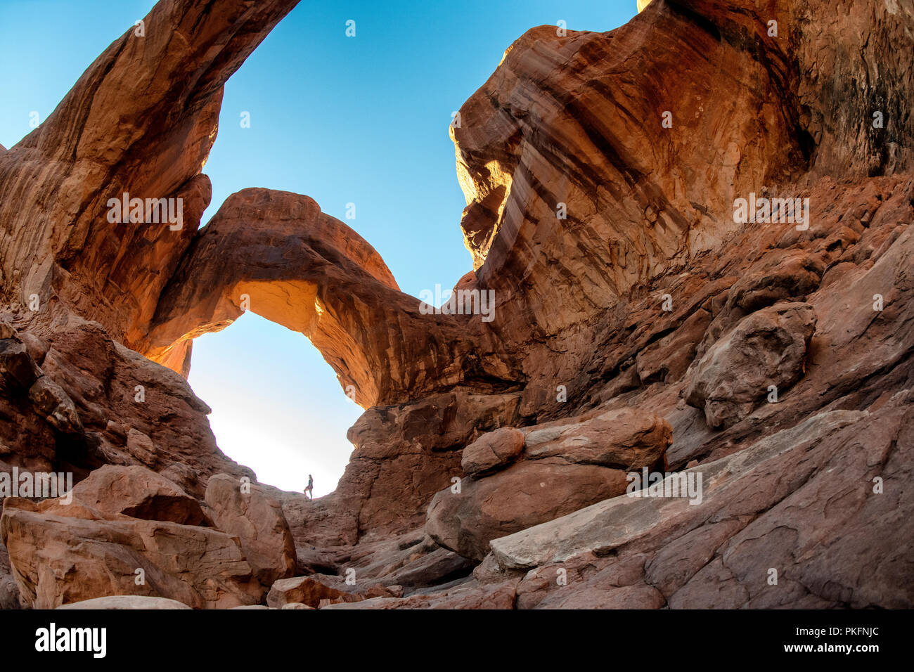 A Woman Stands In Double Arch Arches National Park Moab