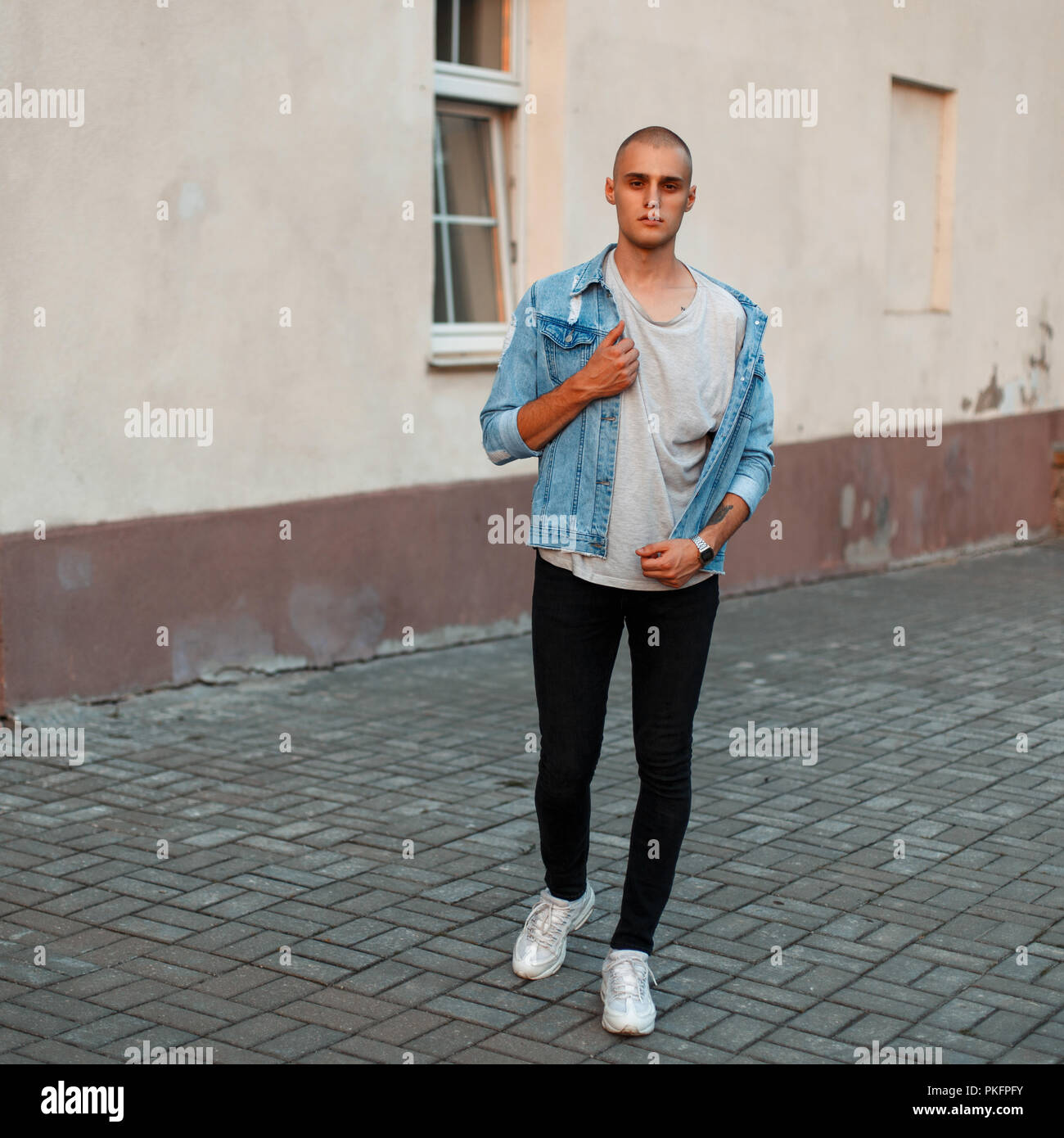 61a73b4ed0 Stylish young man in a denim jacket, a gray T-shirt and black jeans in white  shoes on the street