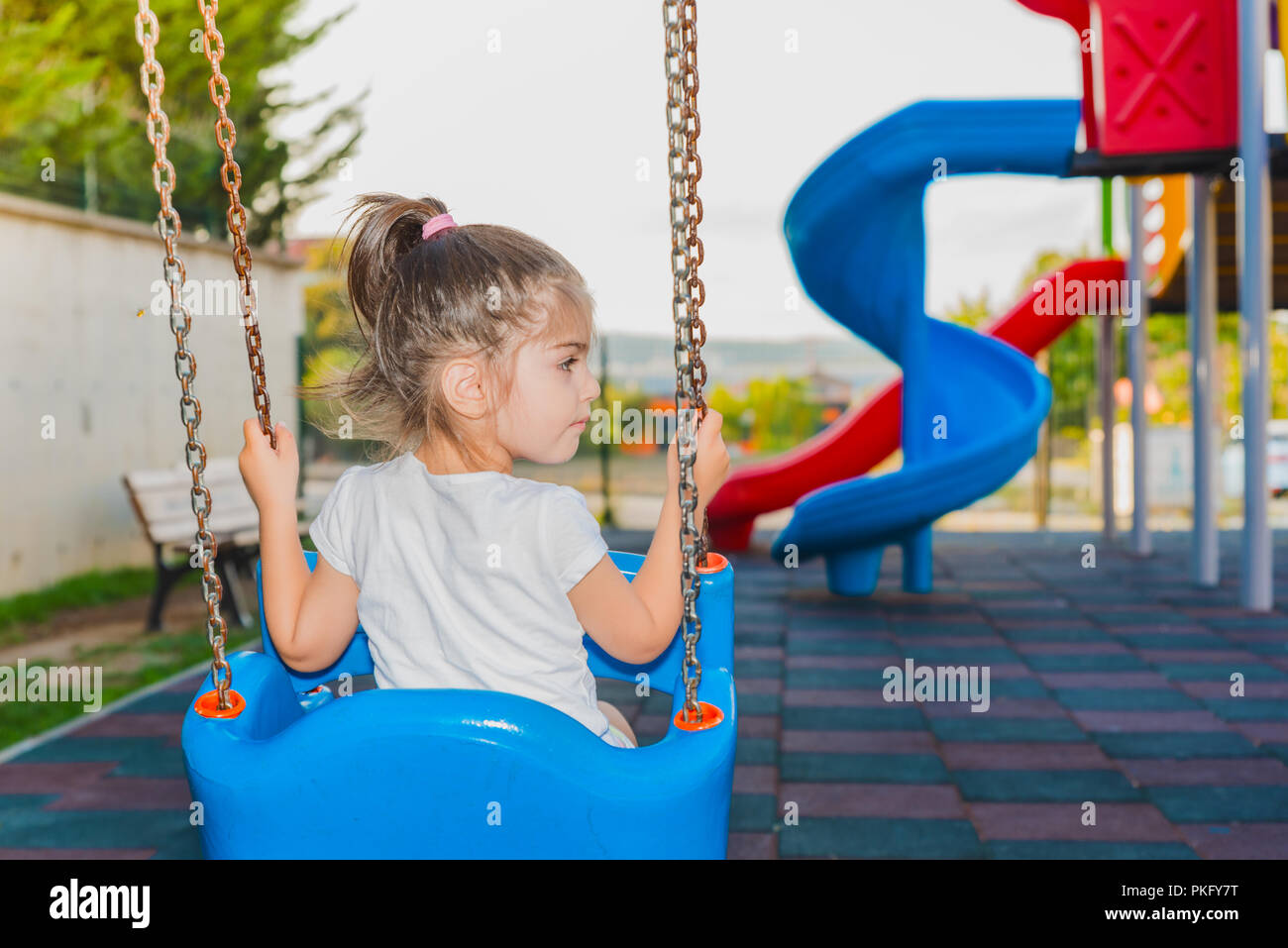 Back view of a cute little girl holding chairs and swinging on playground - Stock Image