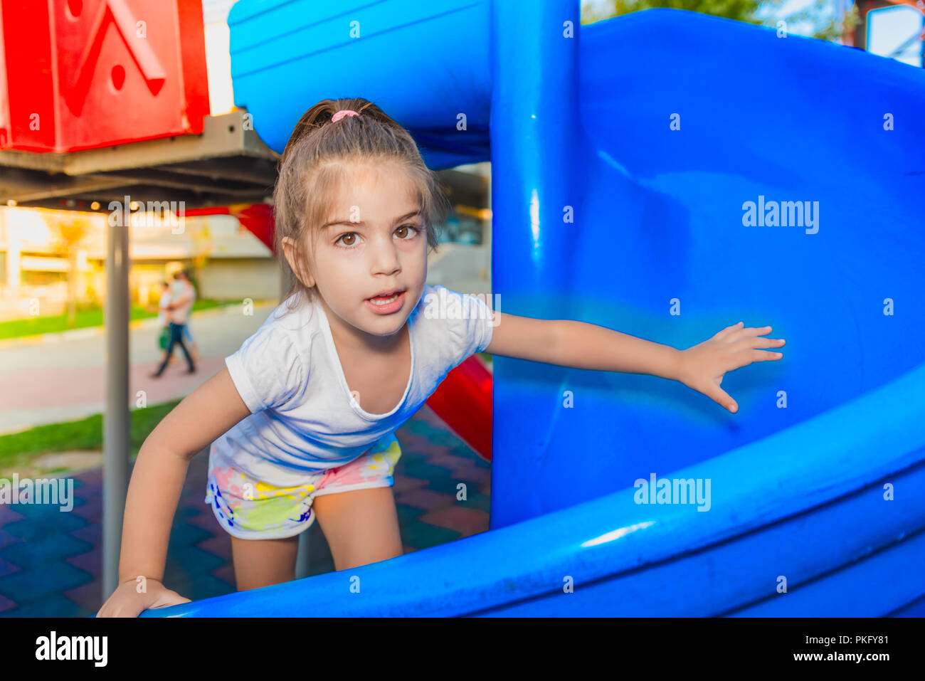Portrait of cute little girl holding and climbing sliders to reach top  on playground - Stock Image