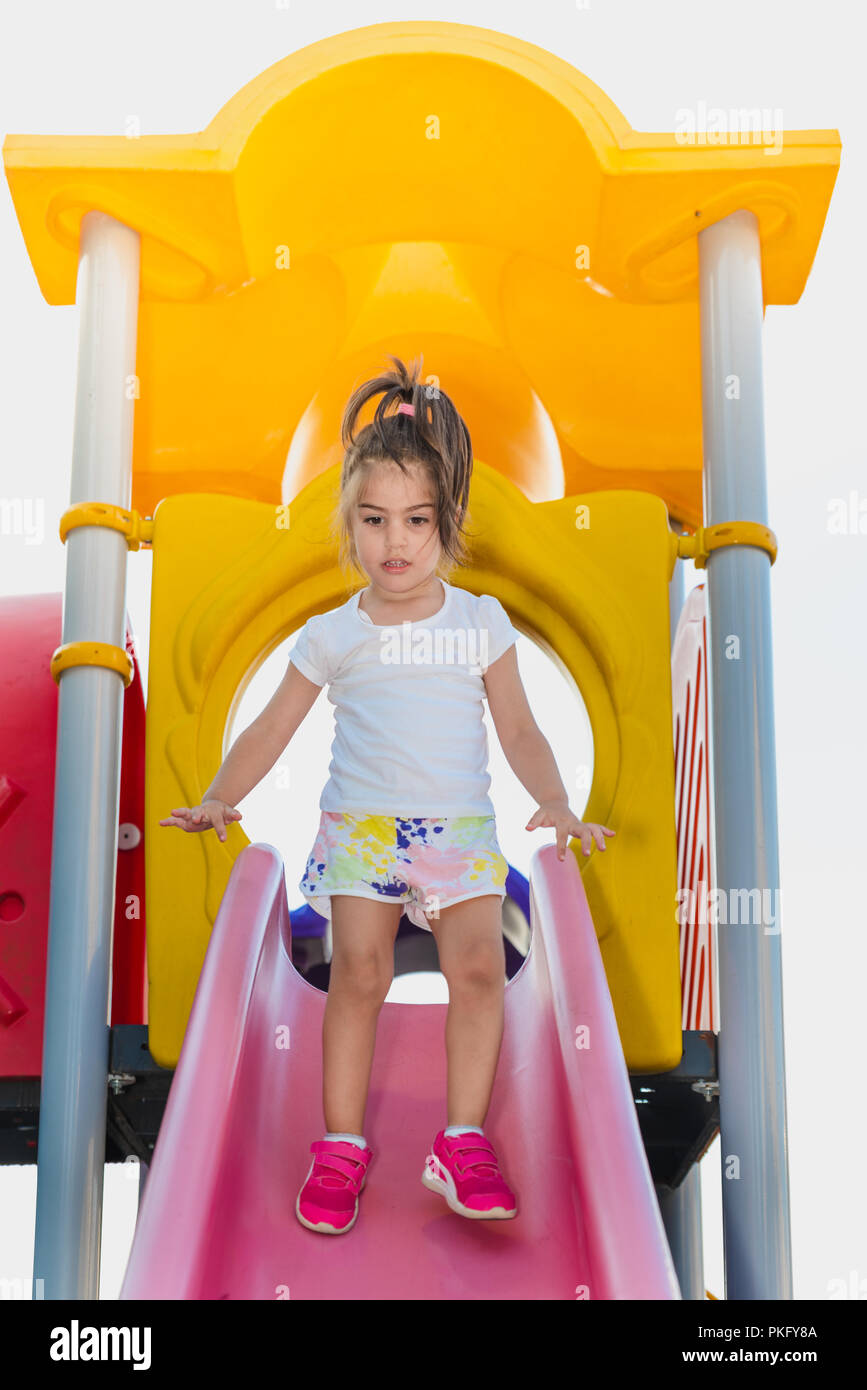 Portrait of cute little girl trying to walk on pink slider from top to bottom on playground - Stock Image