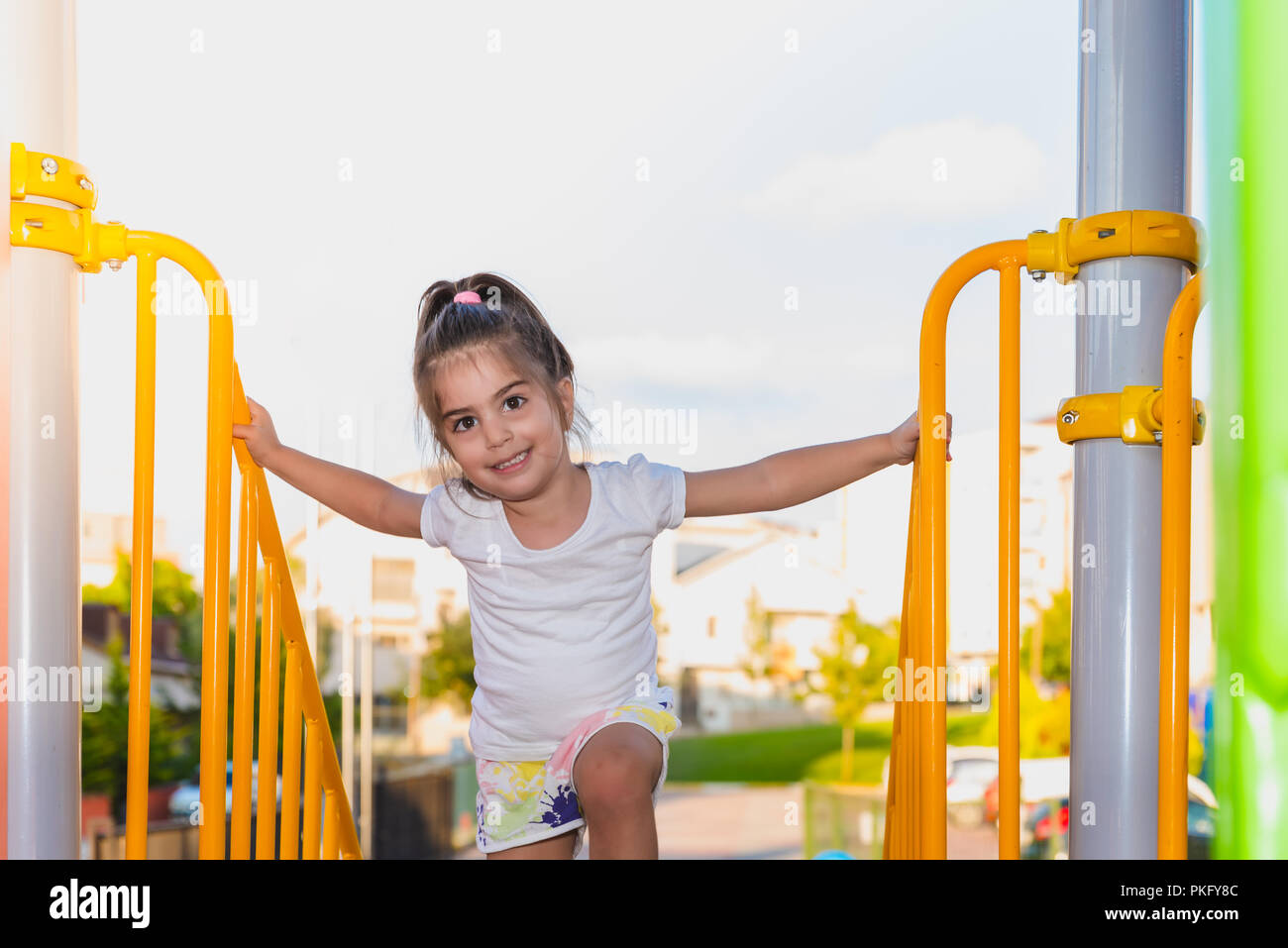 Back side view of cute little girl tying to climb from metallic stairs bars on playground - Stock Image
