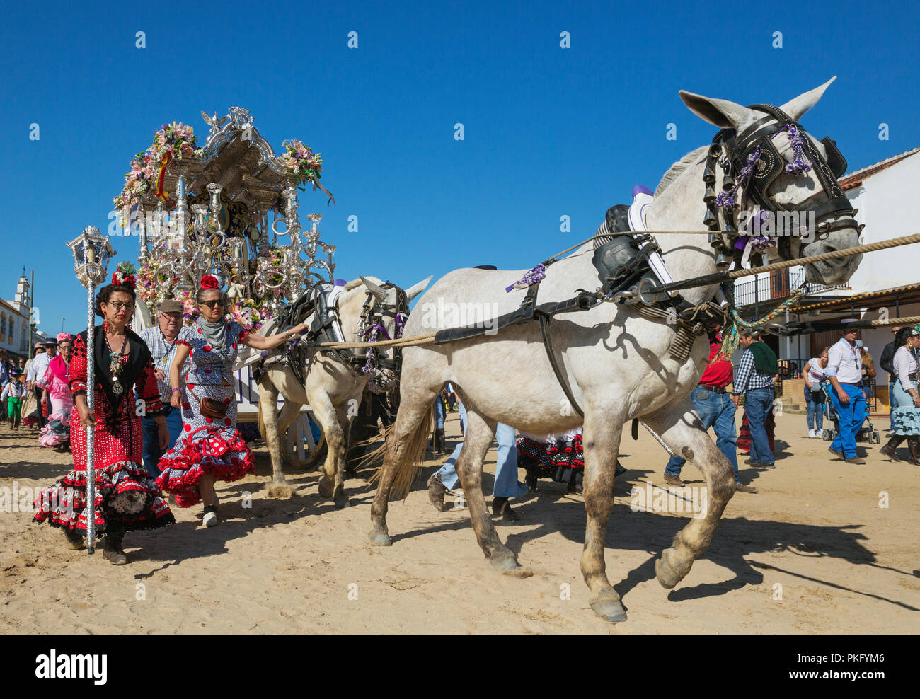 Women wearing colourful gypsy dresses besides a decorated carriage, Pentecost pilgrimage of El Rocio, Huelva province, Andalusia - Stock Image