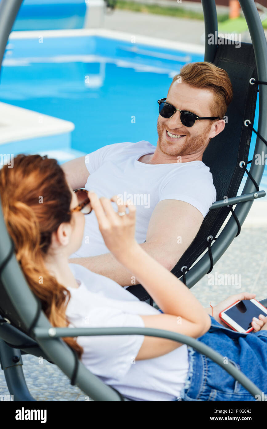 young couple in white t-shirts flirting in front of swimming pool - Stock Image