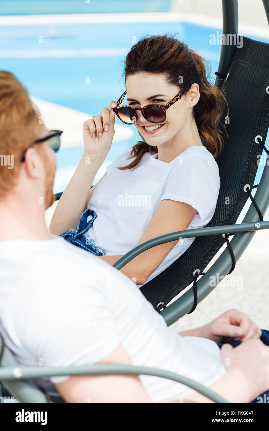 happy young couple in white t-shirts flirting in front of swimming pool - Stock Image