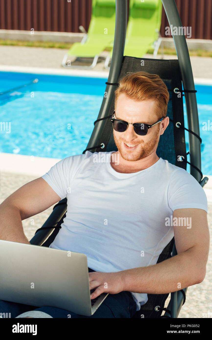 handsome young man sitting in sun lounger in front of swimming pool and working with laptop Stock Photo