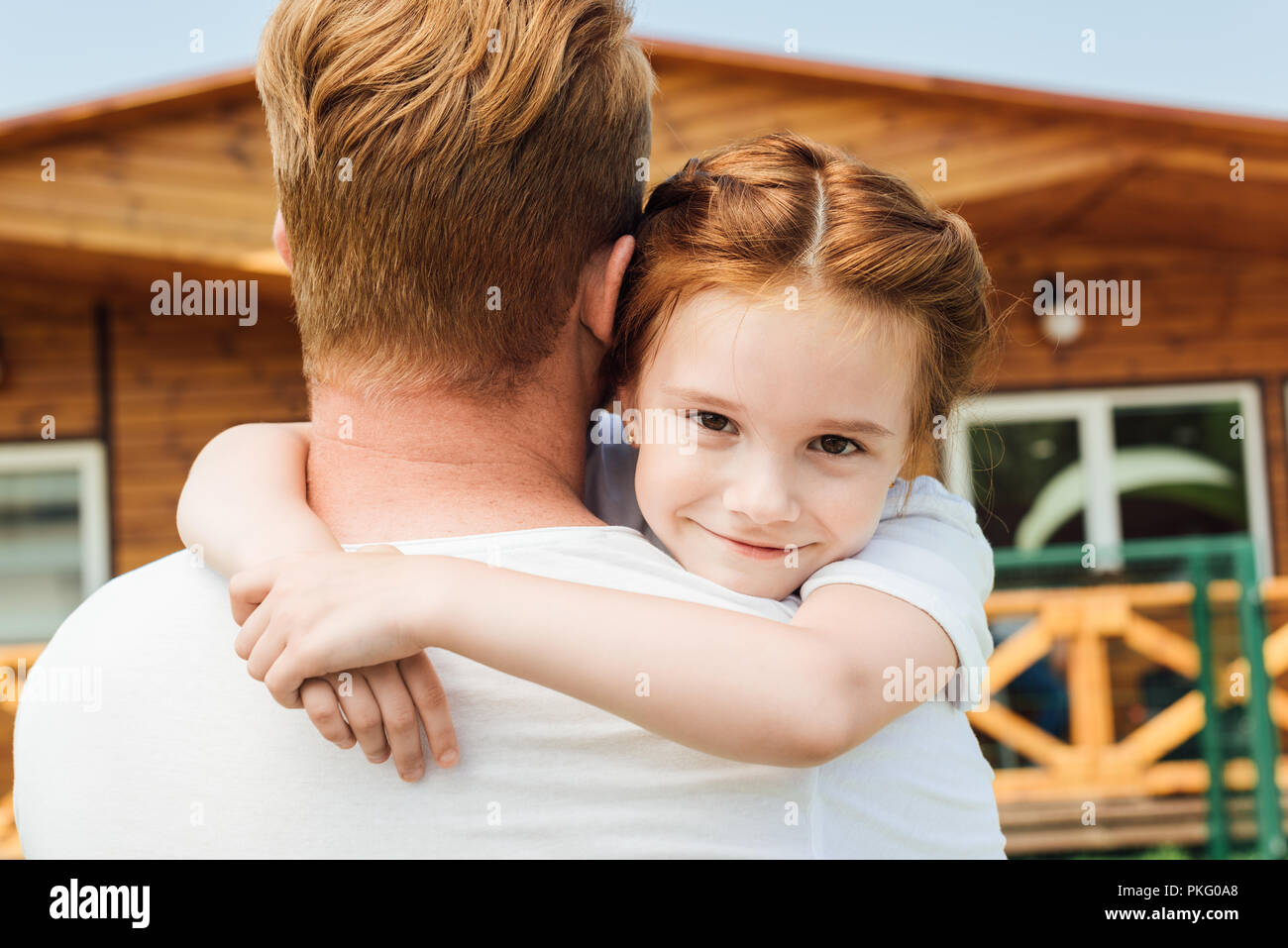 1afc5d49 rear view of father embracing his adorable little daughter while she  looking at camera