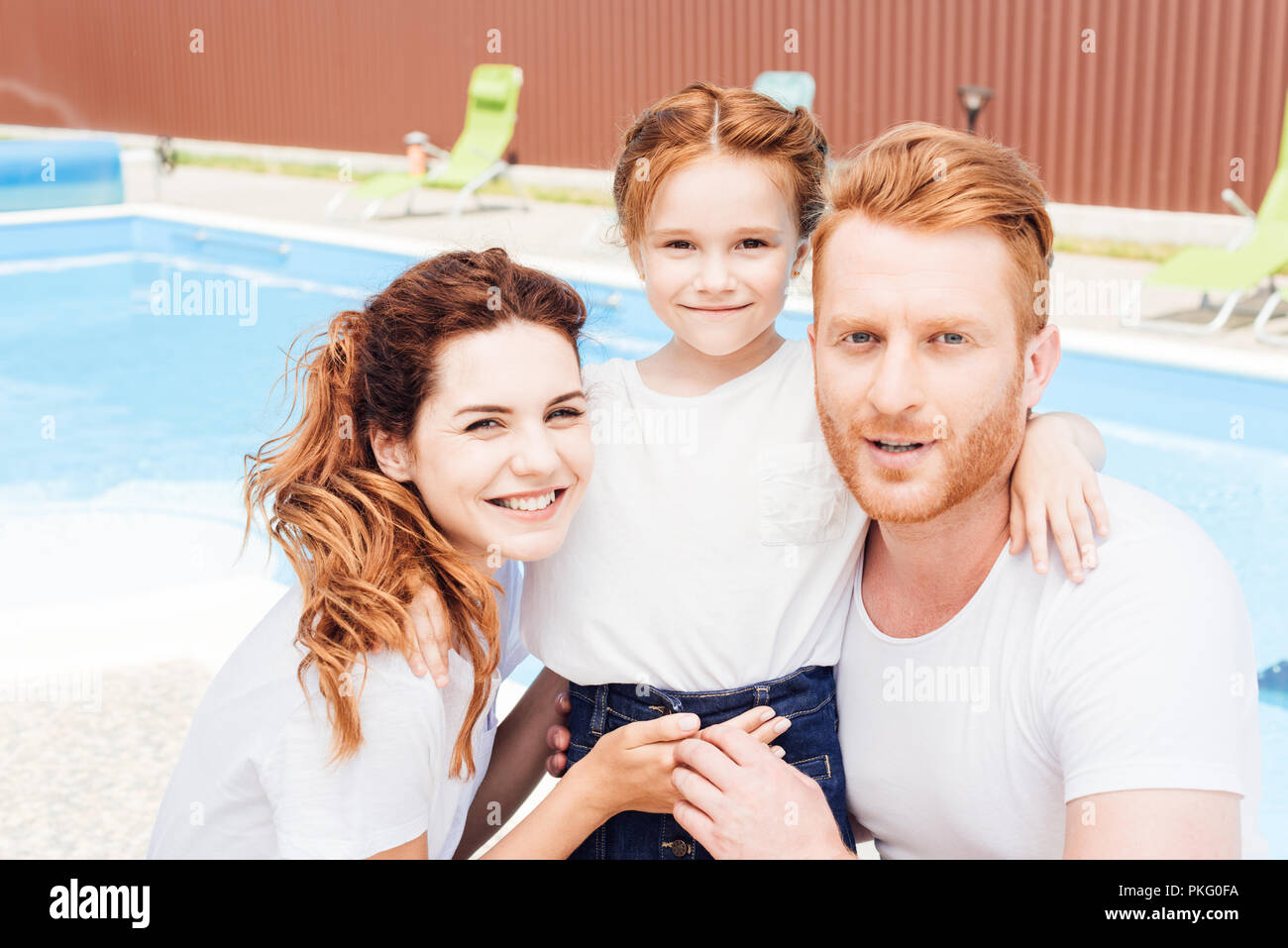 beautiful young family embracing in front of swimming pool and looking at camera - Stock Image