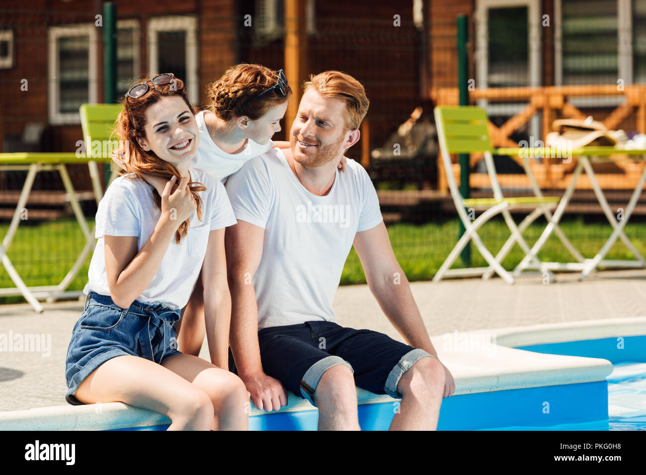 beautiful young family sitting at poolside and embracing together - Stock Image