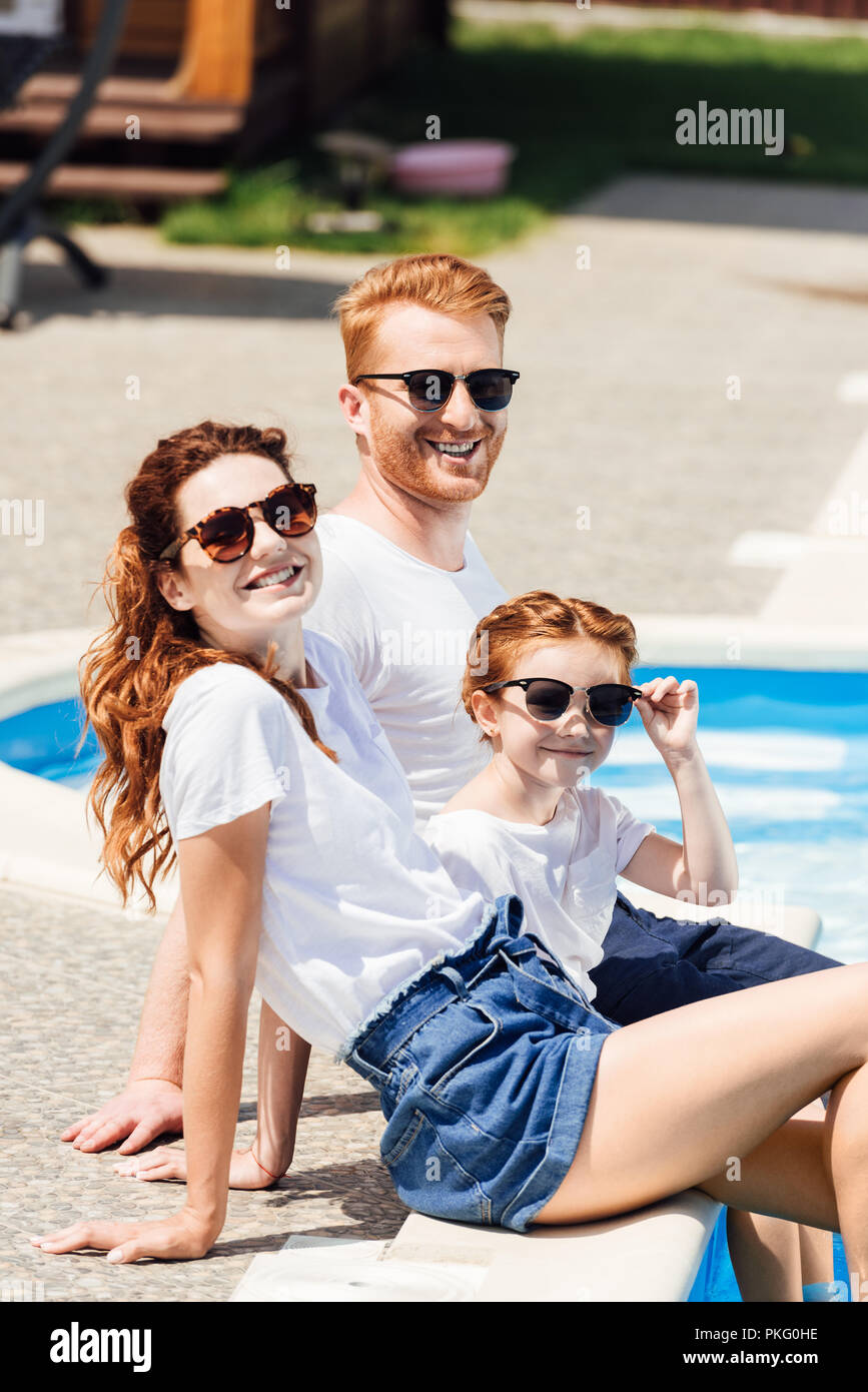beautiful young family in white t-shirts and sunglasses sitting on poolside together and looking at camera - Stock Image