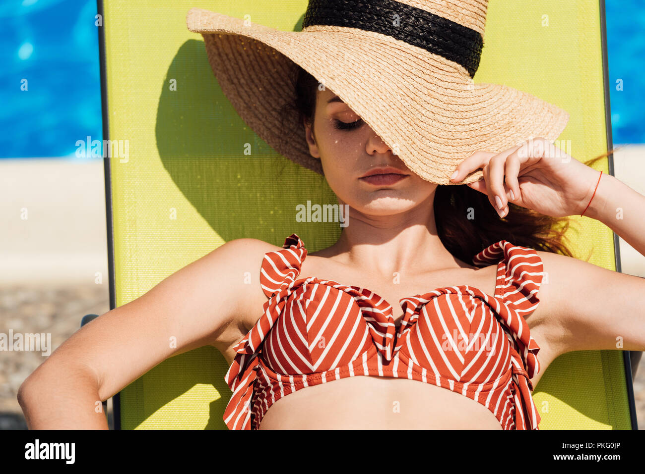 close-up portrait of attractive young woman in straw hat and bikini relaxing on sun lounger at poolside - Stock Image
