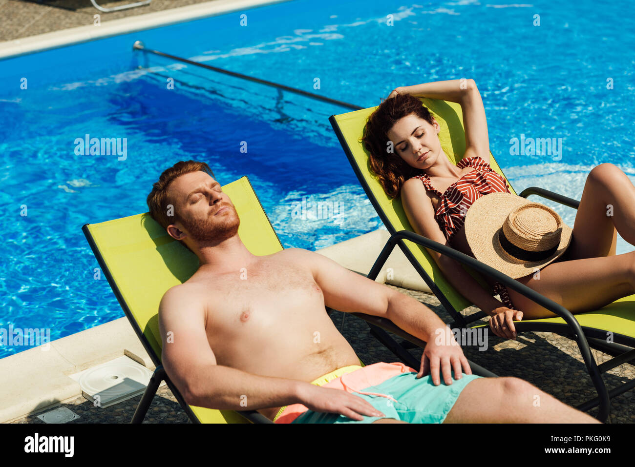 young couple tanning on sun loungers in front of swimming pool - Stock Image