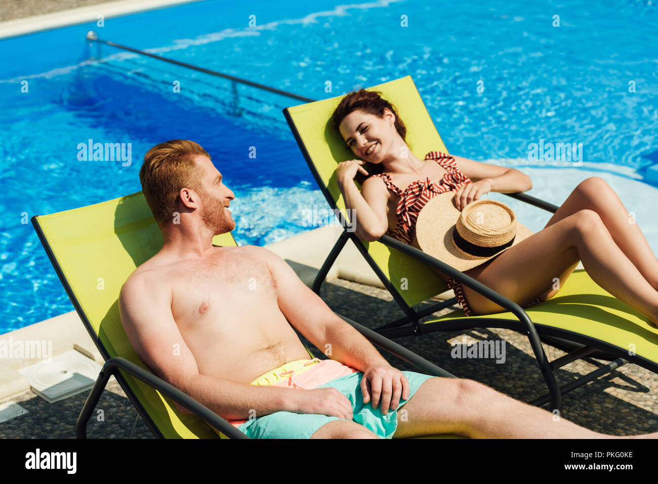 happy young couple flirting while relaxing on sun loungers in front of swimming pool - Stock Image
