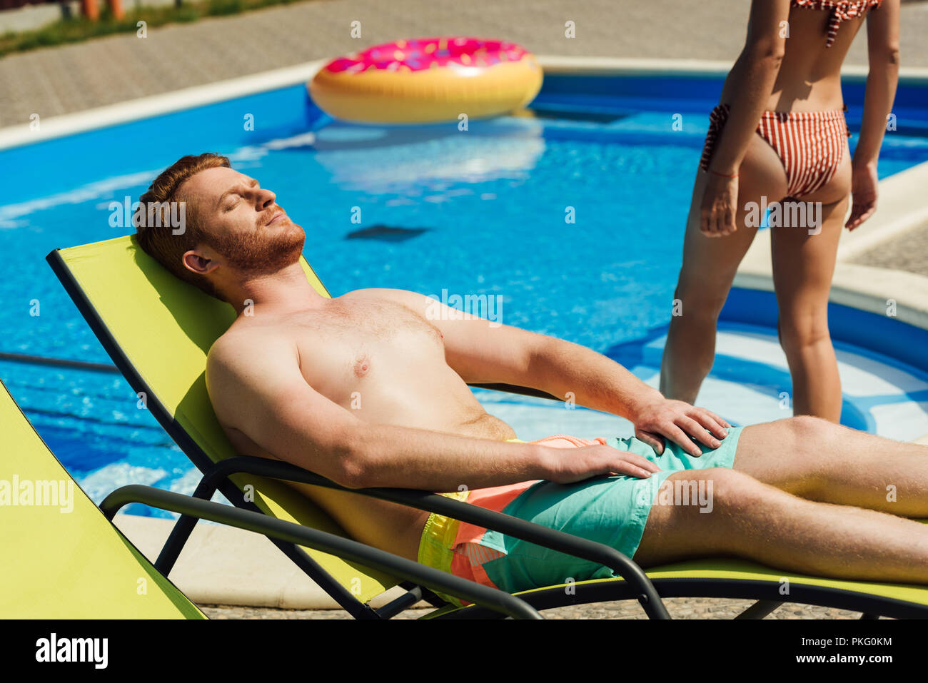 handsome young man tanning on sun lounger while his girlfriend going into swimming pool - Stock Image