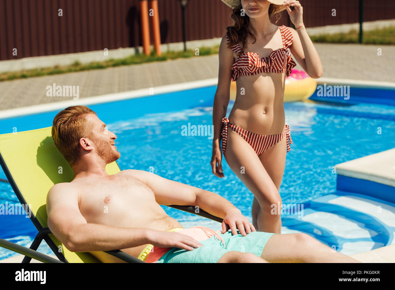 handsome young man tanning on sun lounger while his girlfriend going out of swimming pool - Stock Image