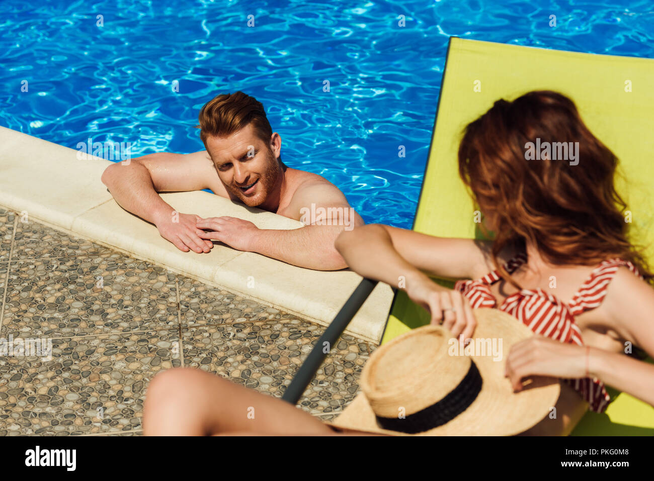 young man flirting with woman lying on sun lounger while swimming in pool - Stock Image