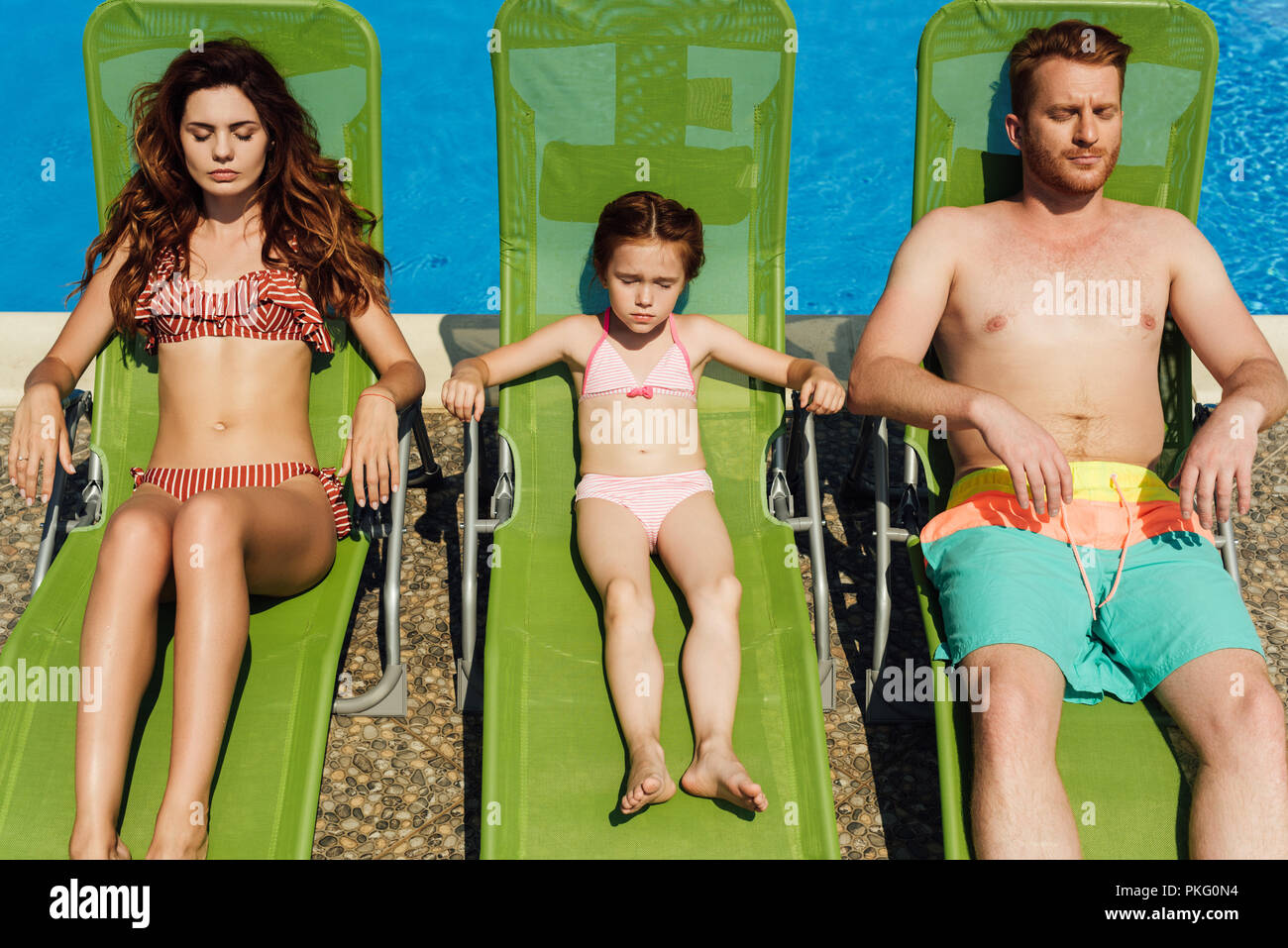 relaxed young family tanning on sun loungers together - Stock Image