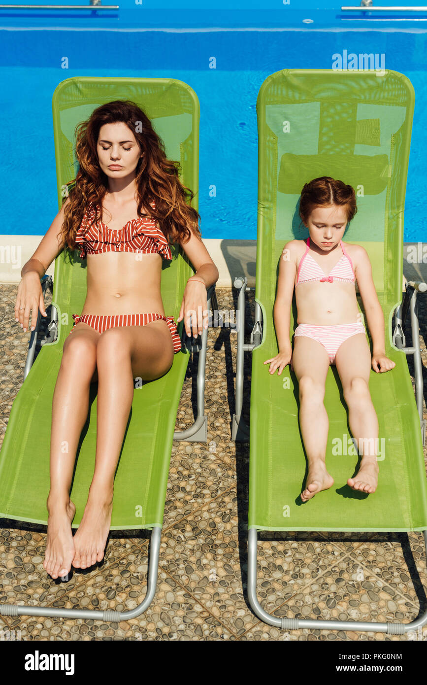 beautiful young mother and daughter relaxing on sun loungers on poolside - Stock Image