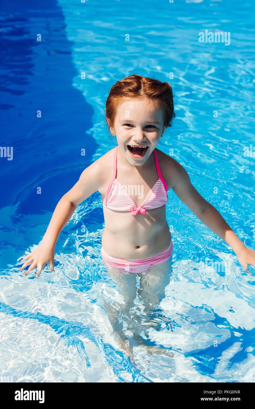 laughing little child in bikini in swimming pool - Stock Image