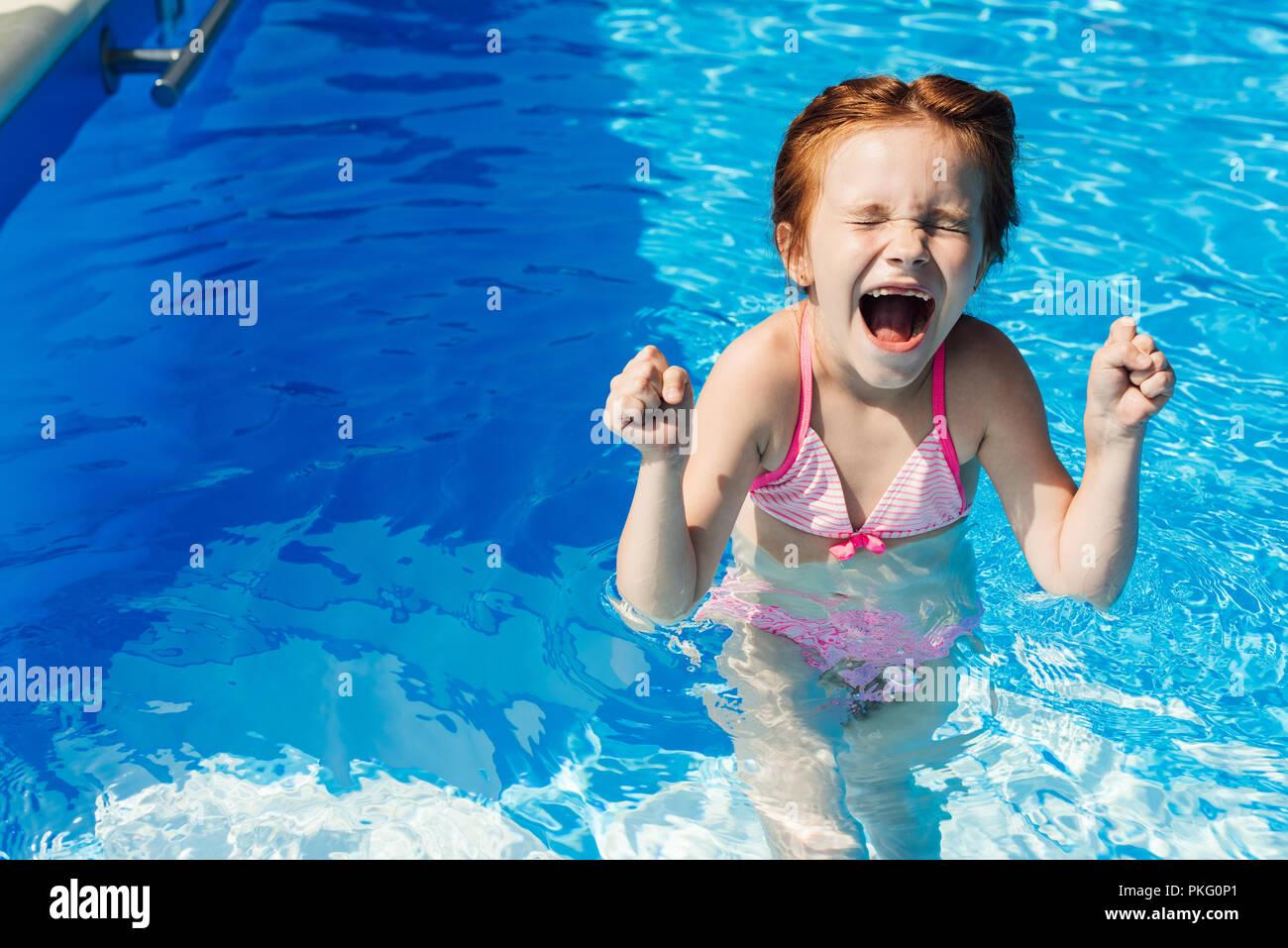 screaming little child in bikini in swimming pool - Stock Image