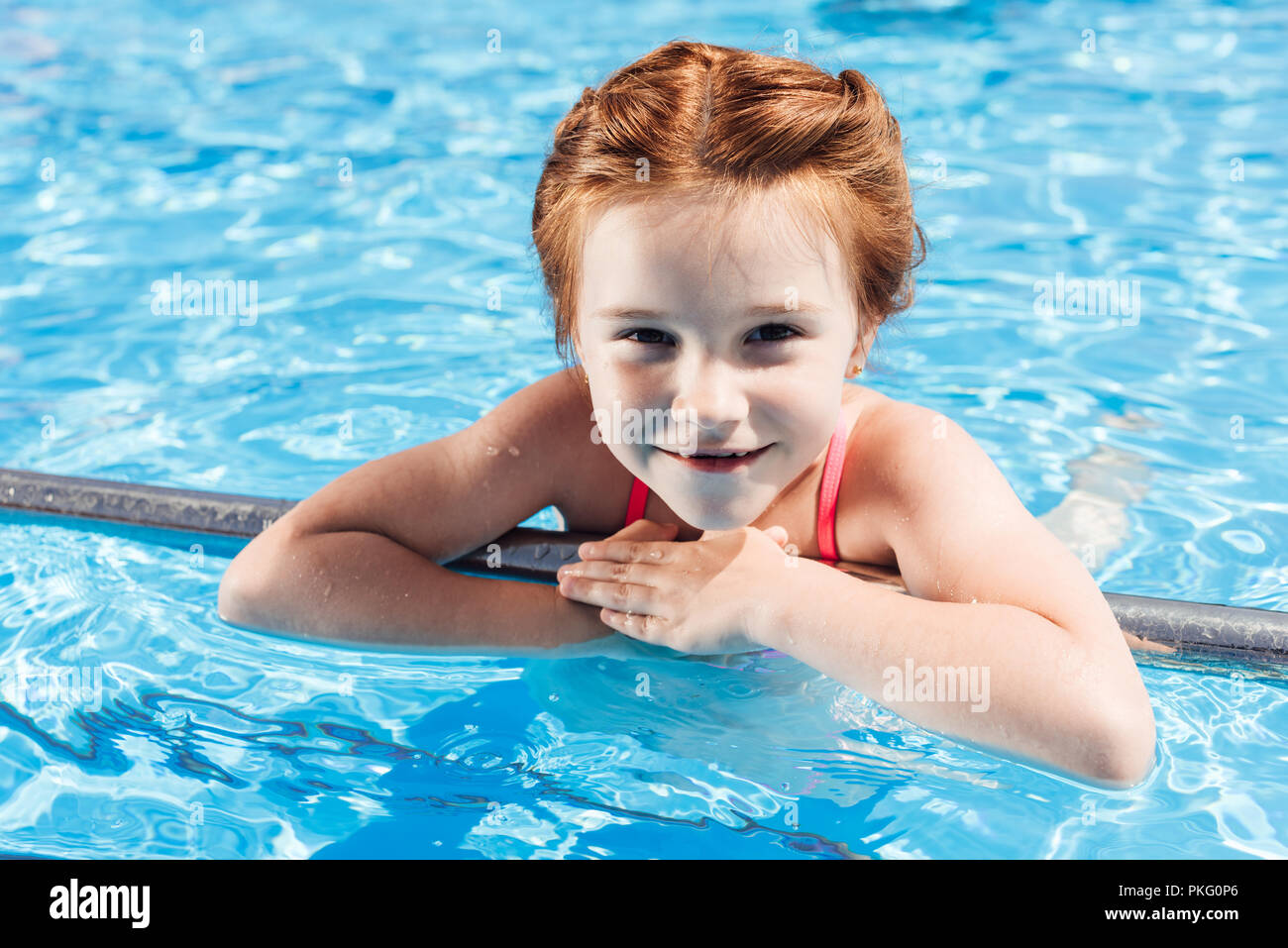 close-up portrait of happy little child in bikini in swimming pool looking at camera - Stock Image