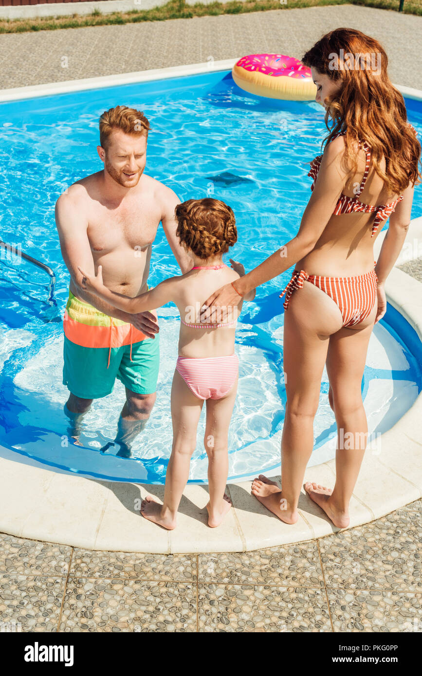 beautiful young family spending time together at poolside - Stock Image