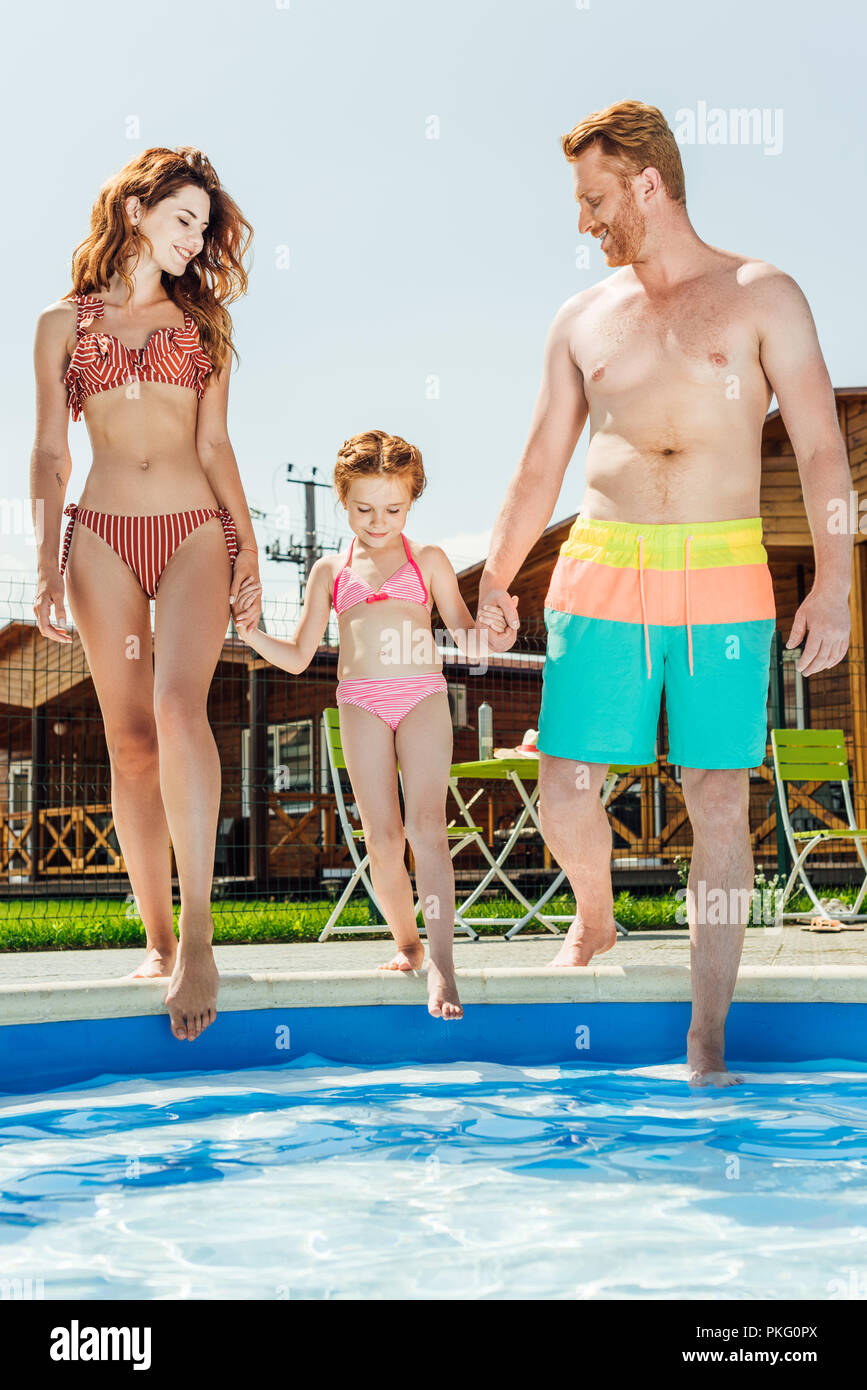 happy young family going into swimming pool - Stock Image