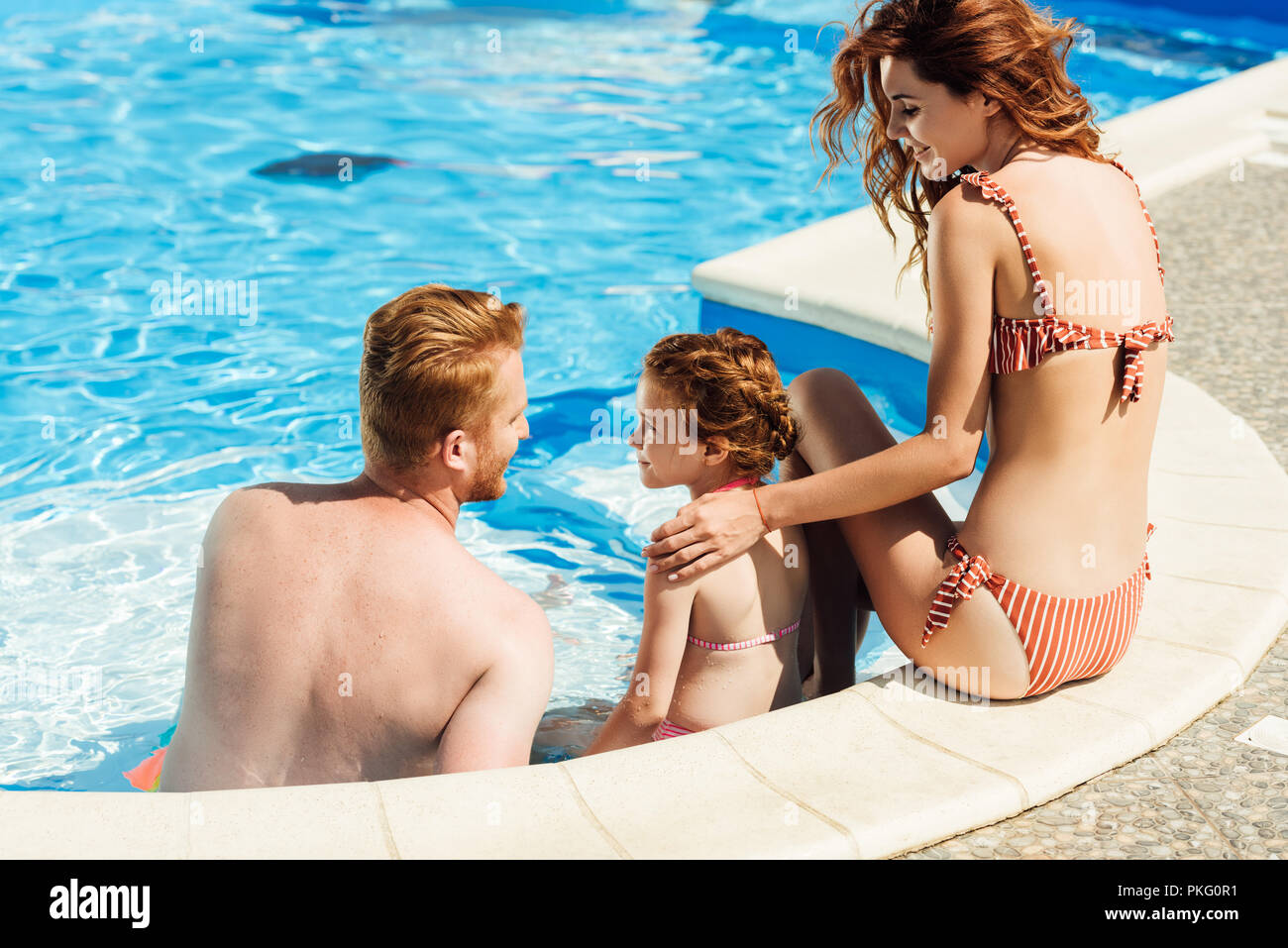 rear view of beautiful young family sitting at poolside together - Stock Image