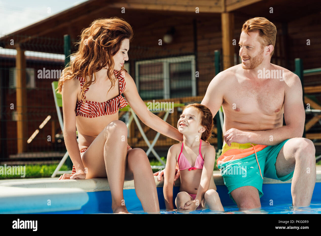 beautiful young family sitting at poolside together - Stock Image