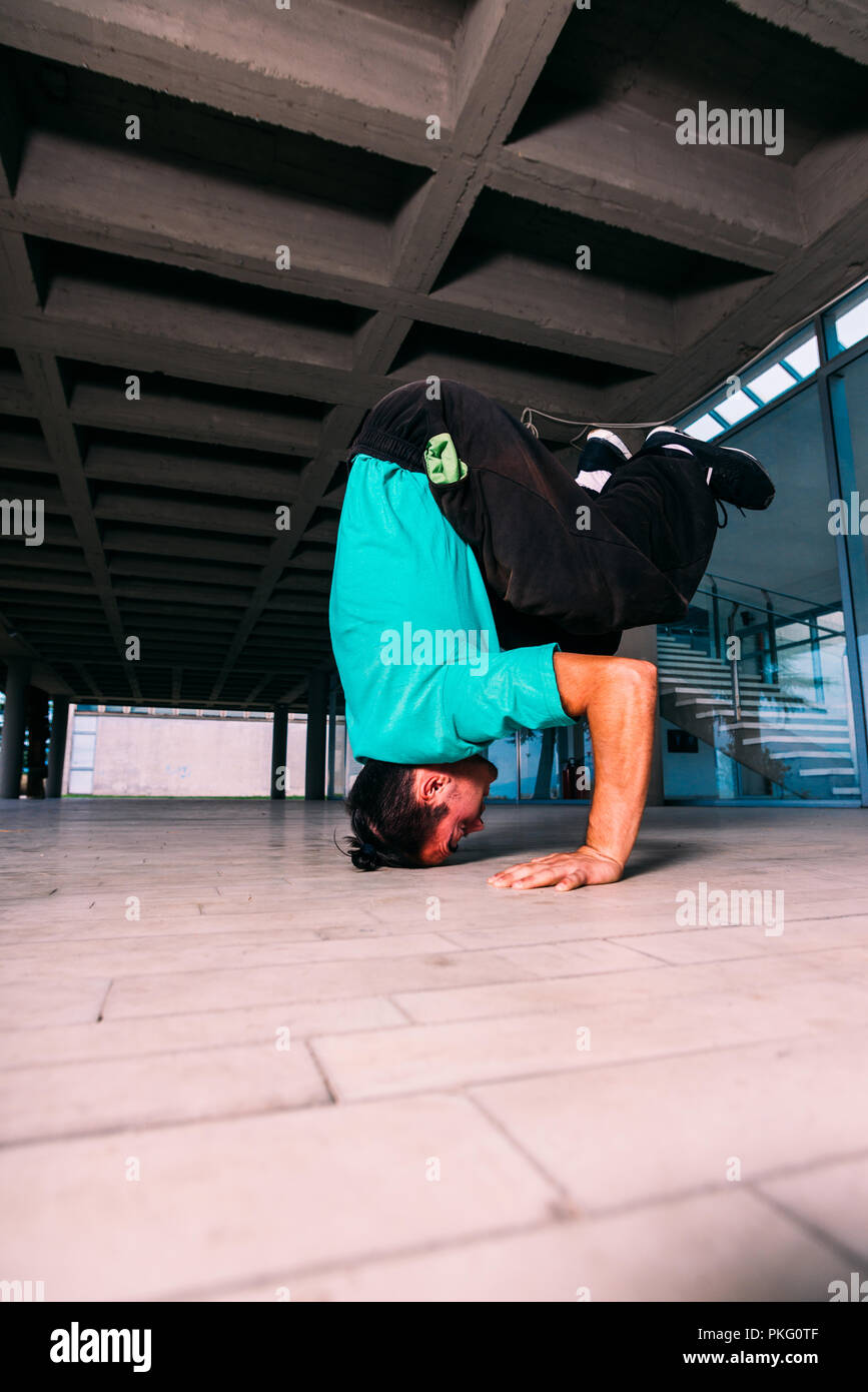 Young man doing headstand while trains parkour - Stock Image