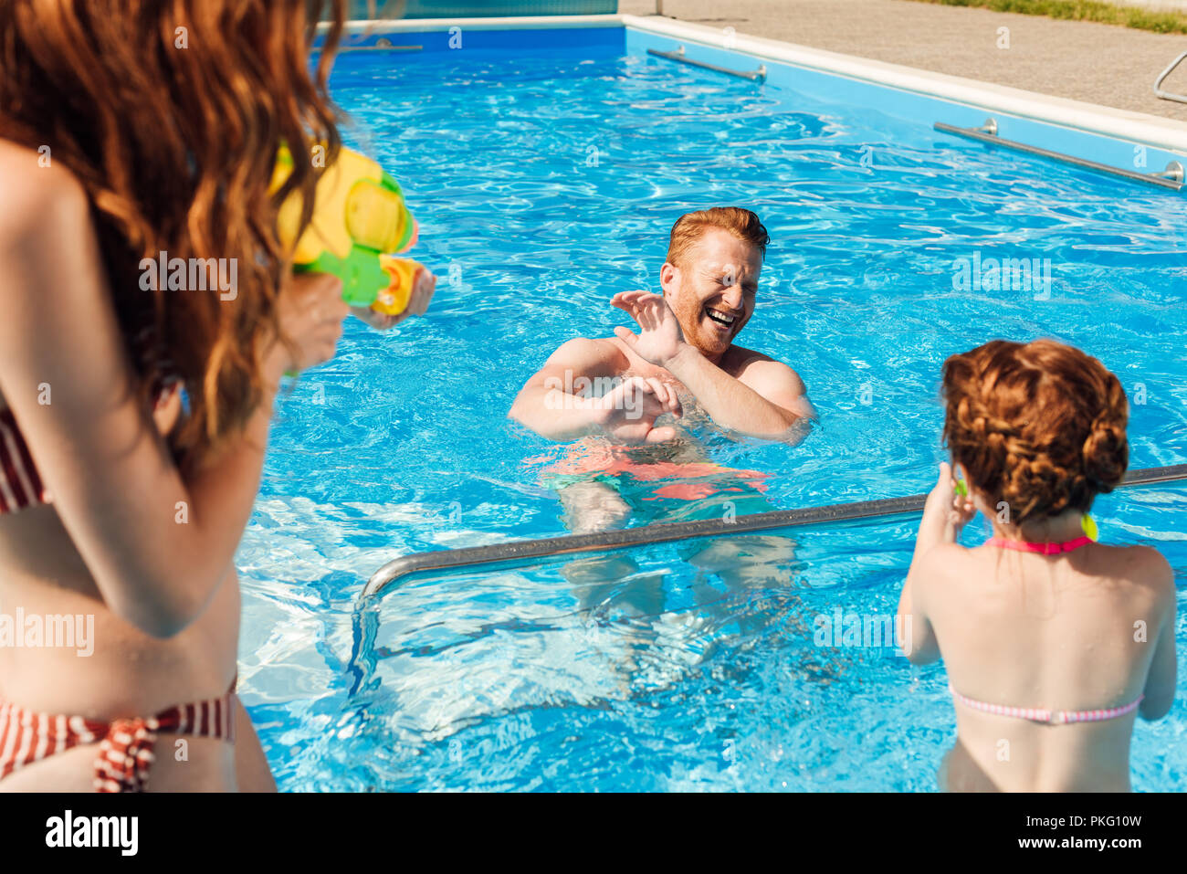 happy young family playing in swimming pool - Stock Image