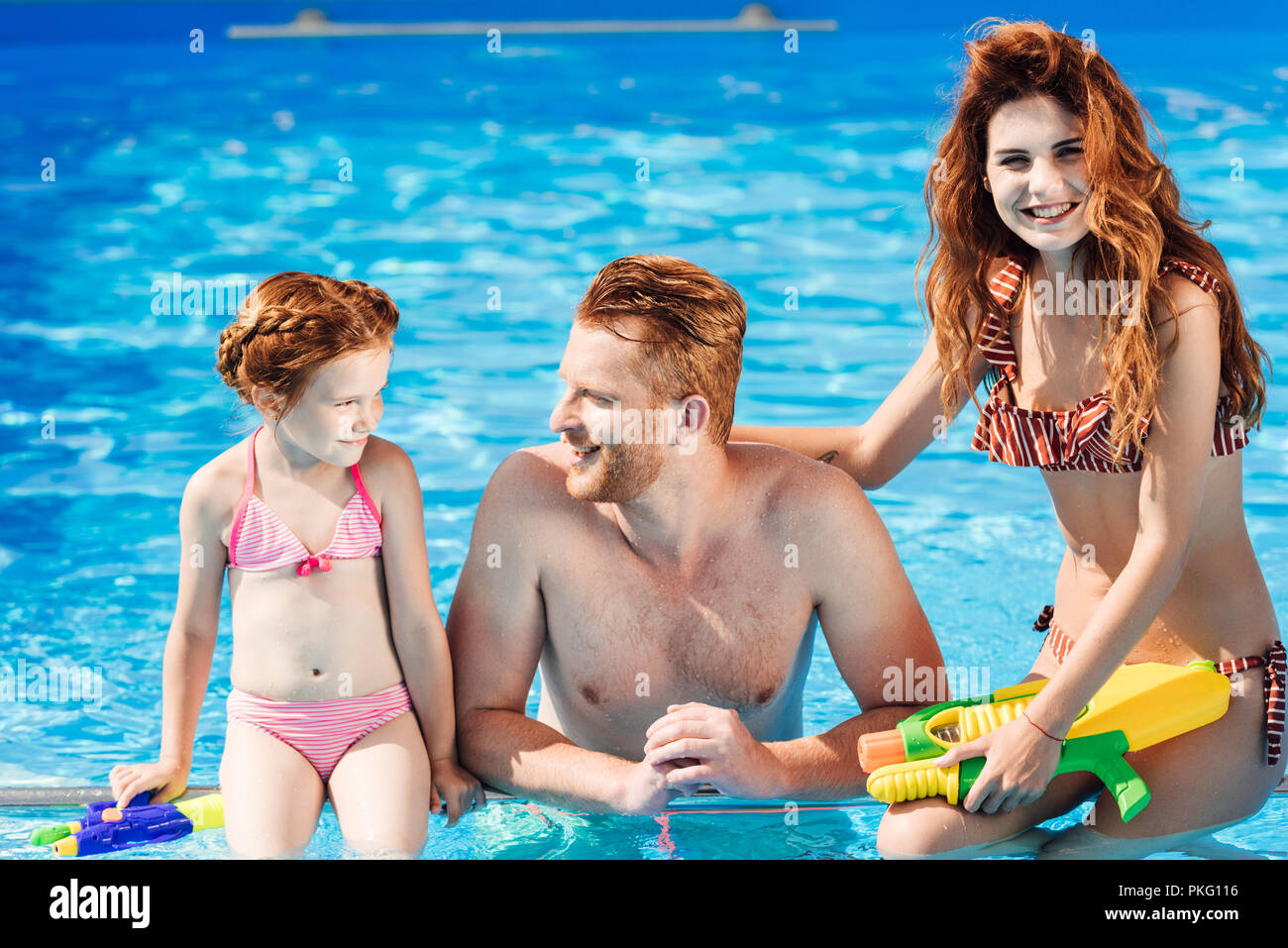 beautiful young family spending time at swimming pool - Stock Image