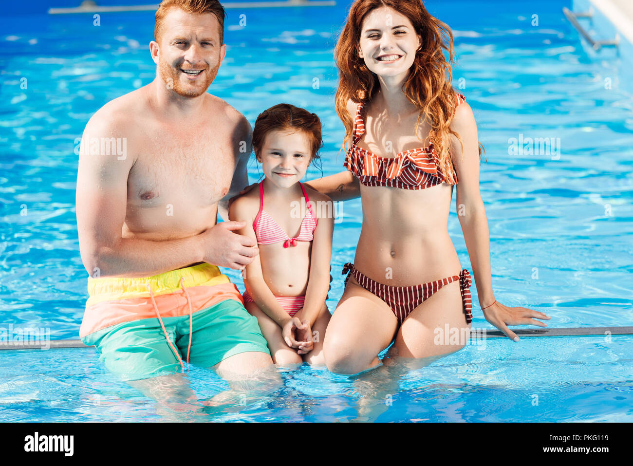 beautiful young family spending time at swimming pool and looking at camera - Stock Image