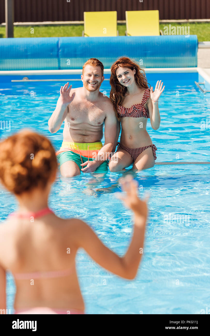rear view of little girl waving to parents at swimming pool - Stock Image