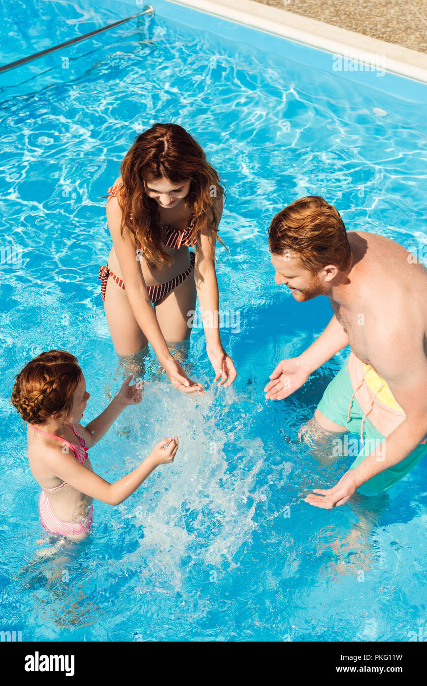 high angle view of beautiful young family playing in swimming pool - Stock Image
