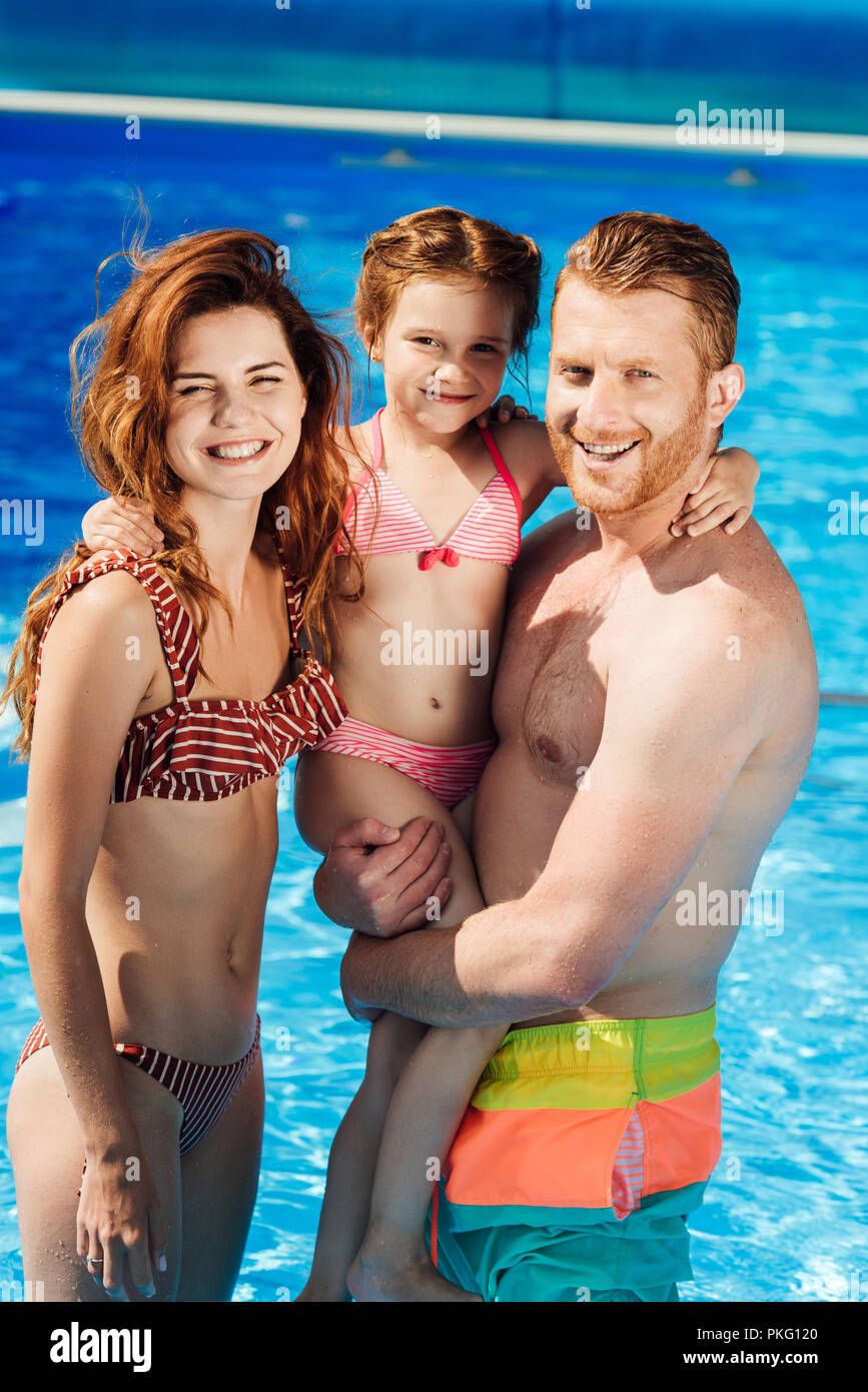 beautiful young family embracing in swimming pool and looking at camera - Stock Image