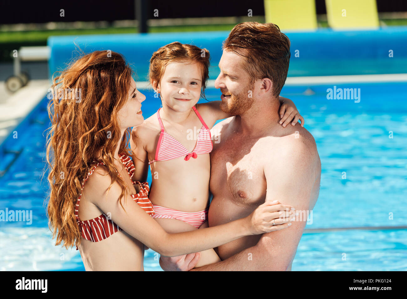 beautiful young family embracing in swimming pool - Stock Image