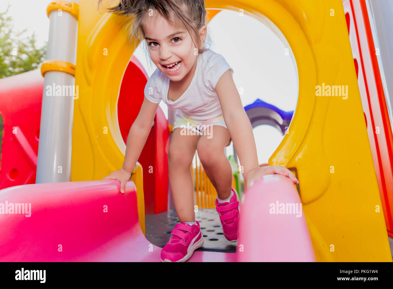 Portrait of cute little girl holding  and sliding on sliders on playground - Stock Image
