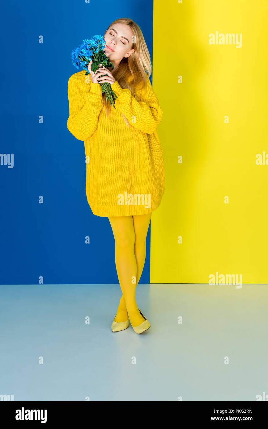 Attractive blonde woman in yellow outfit holding blue flowers on blue and  yellow background d71ba8bdc