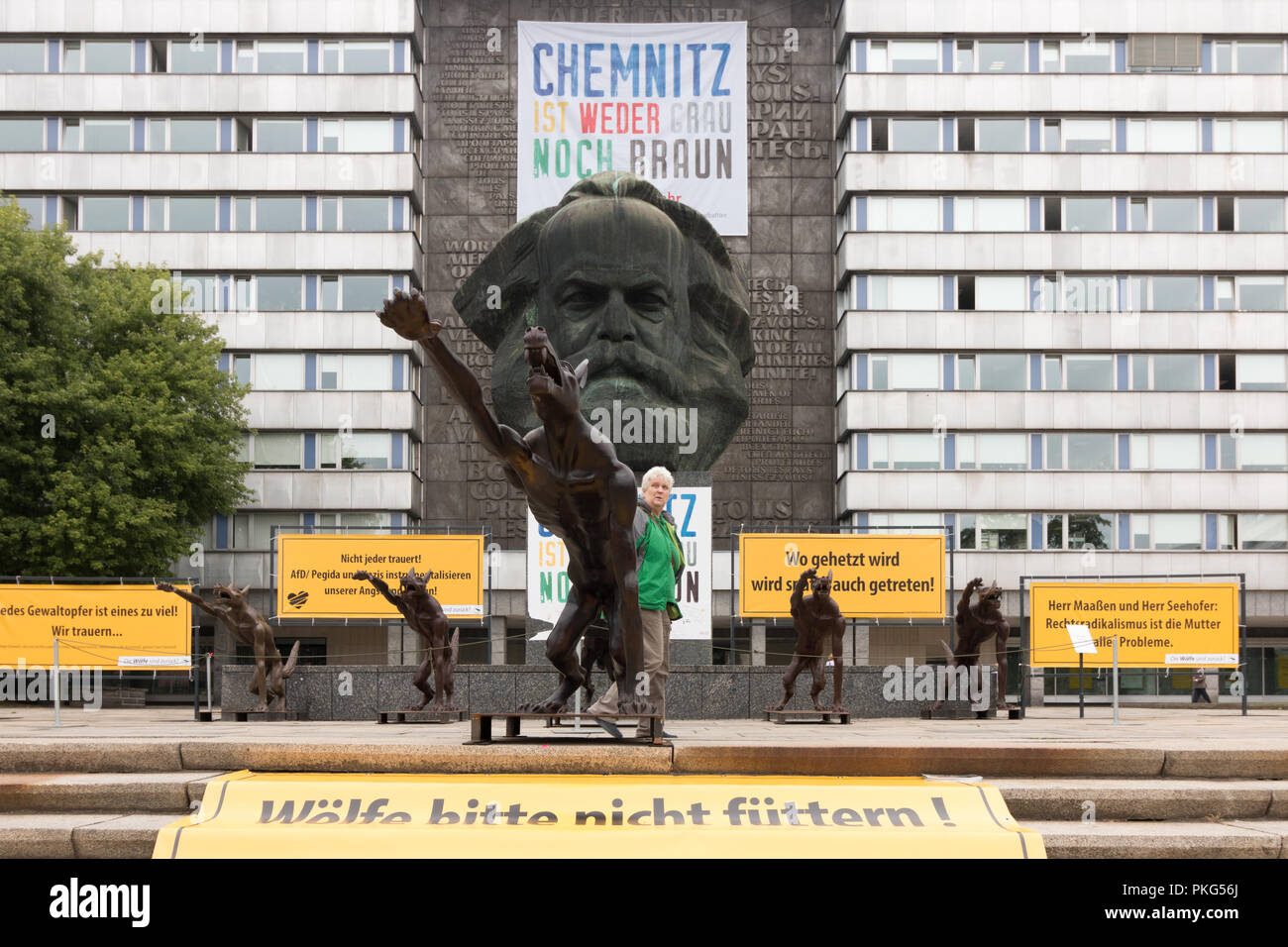Chemnitz, Germany - September 13, 2018: A passer-by takes a look at a brass wolf saluting Heil Hitler with the National Socialists' greeting. The installation by the artist Rainer Opolka, which was set up today, is intended to counter a sign against hatred and violence after the great right-wing demonstrations a good two weeks after the murder of a German in Chemnitz by refugees. Credit: Mattis Kaminer/Alamy Live News - Stock Image