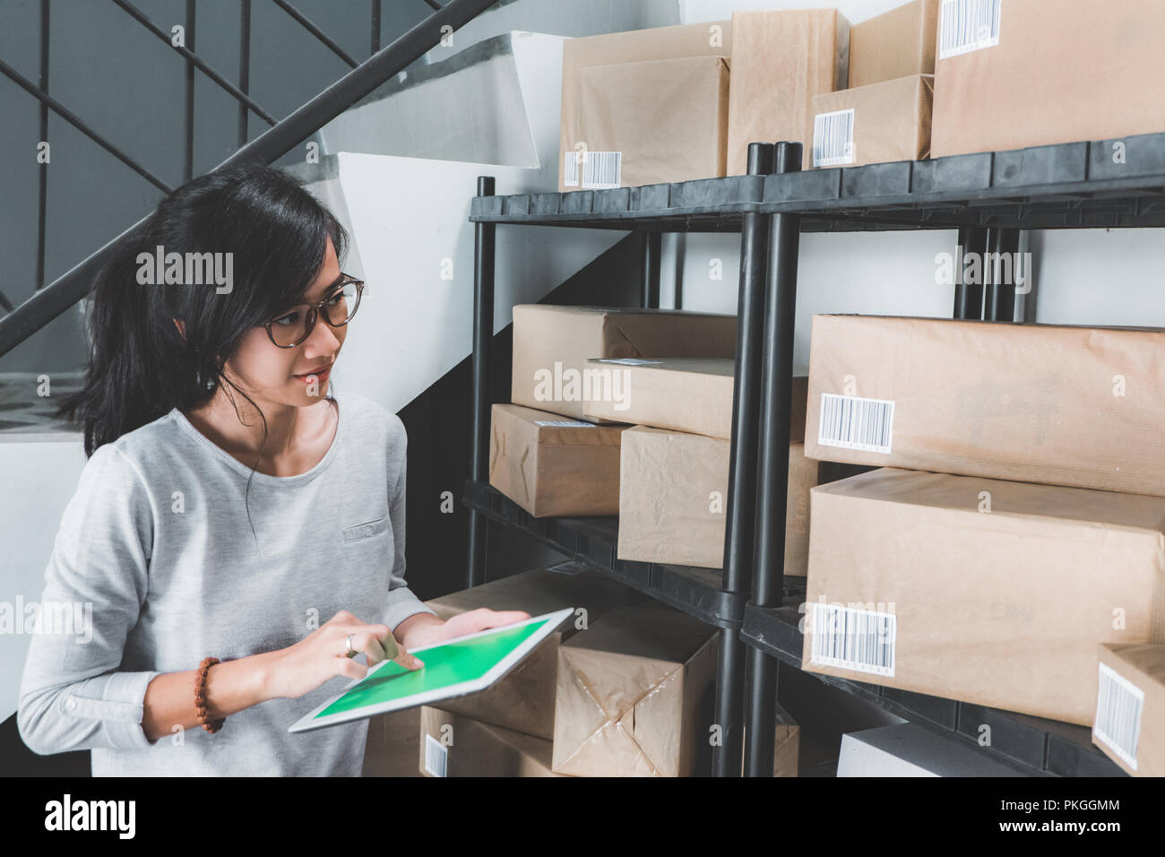 woman counting on package on a shelf - Stock Image