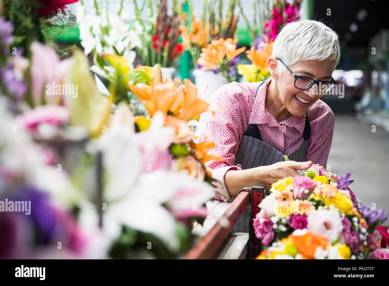 Charrming senior woman arranges flowers on local market - Stock Image